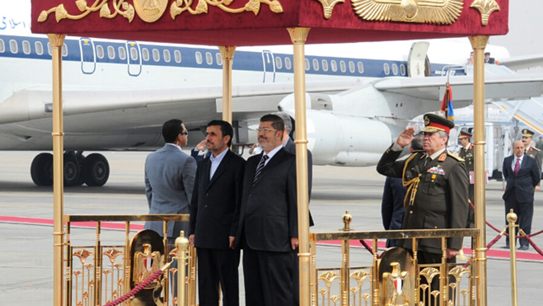 Feb. 5, 2013: In this image released by the Egyptian Presidency, Iran's President Mahmoud Ahmadinejad, center, and Egyptian President Mohammed Morsi, center right, participate in an arrival ceremony at the airport in Cairo, Egypt.