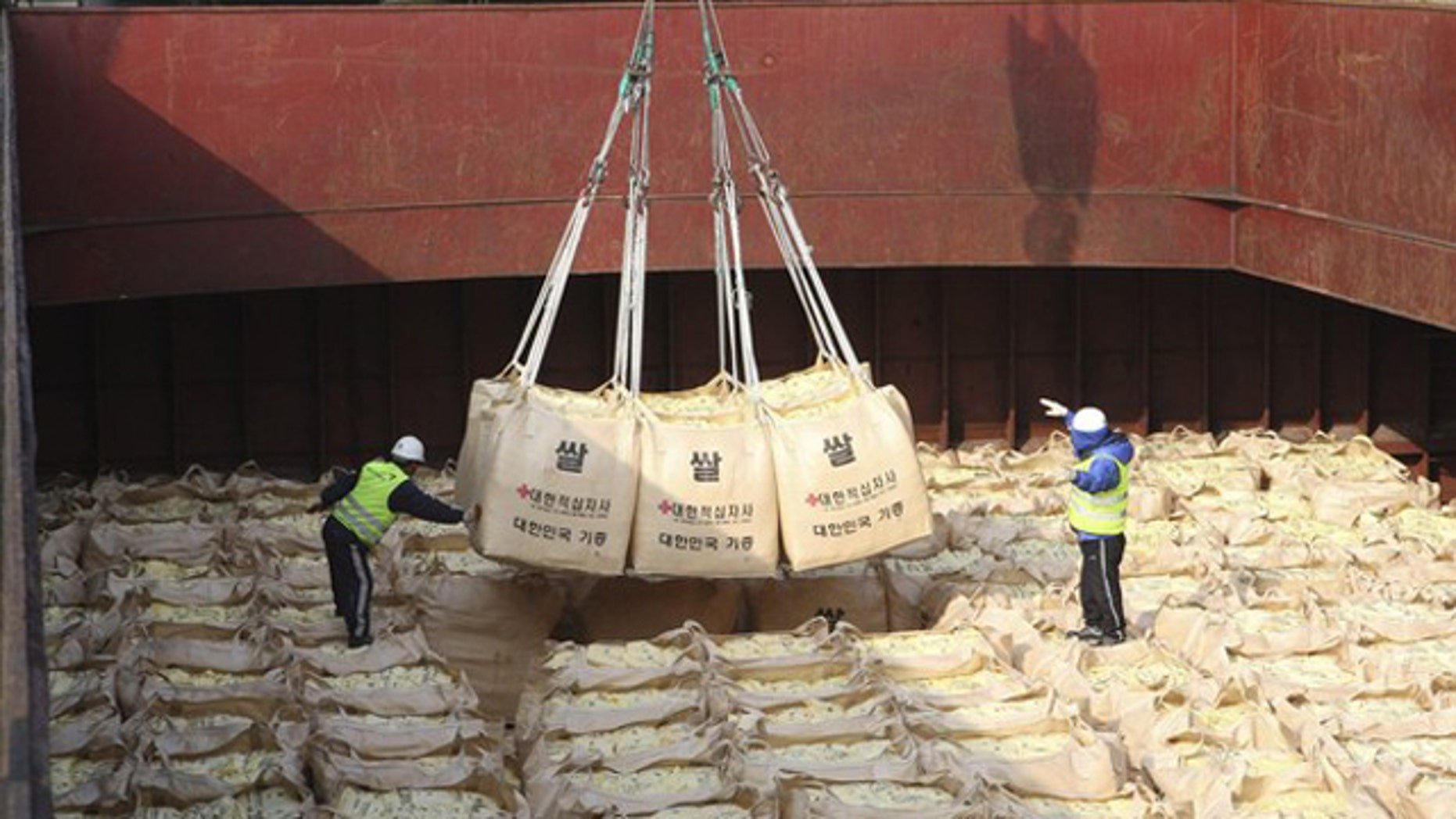 Workers load packs of rice as food aid for flood-stricken North Koreans onto a ship at a port in Gunsan, about 168 miles south of Seoul, Oct. 22, 2010.