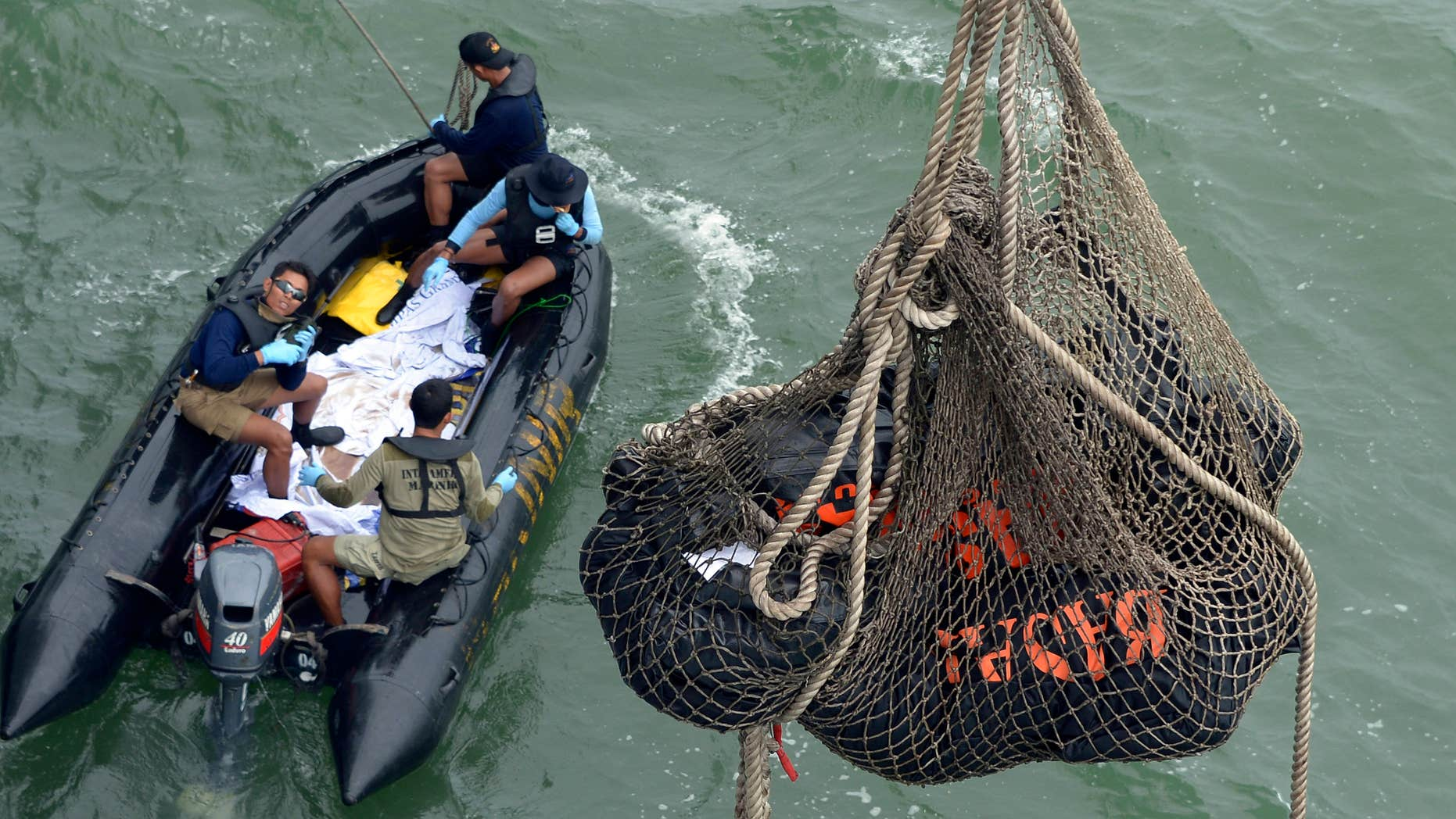 Jan. 3, 2015: Bags containing dead bodies of the passengers of AirAsia Flight 8501 are lifted to Indonesian navy vessel KRI Banda Aceh at sea off the coast of Pangkalan Bun, Indonesia
