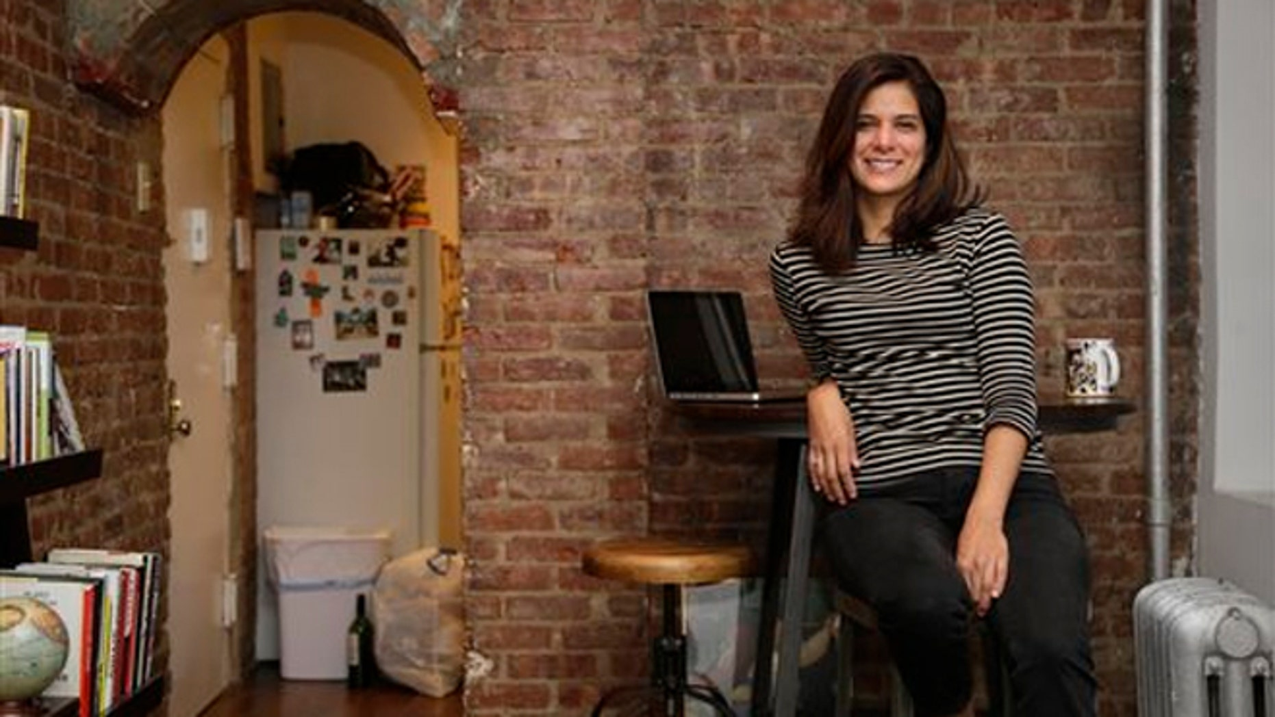Oct. 10, 2013:  Mishelle Farer poses for picture in her apartment, where she rents a room on Airbnb, in New York.