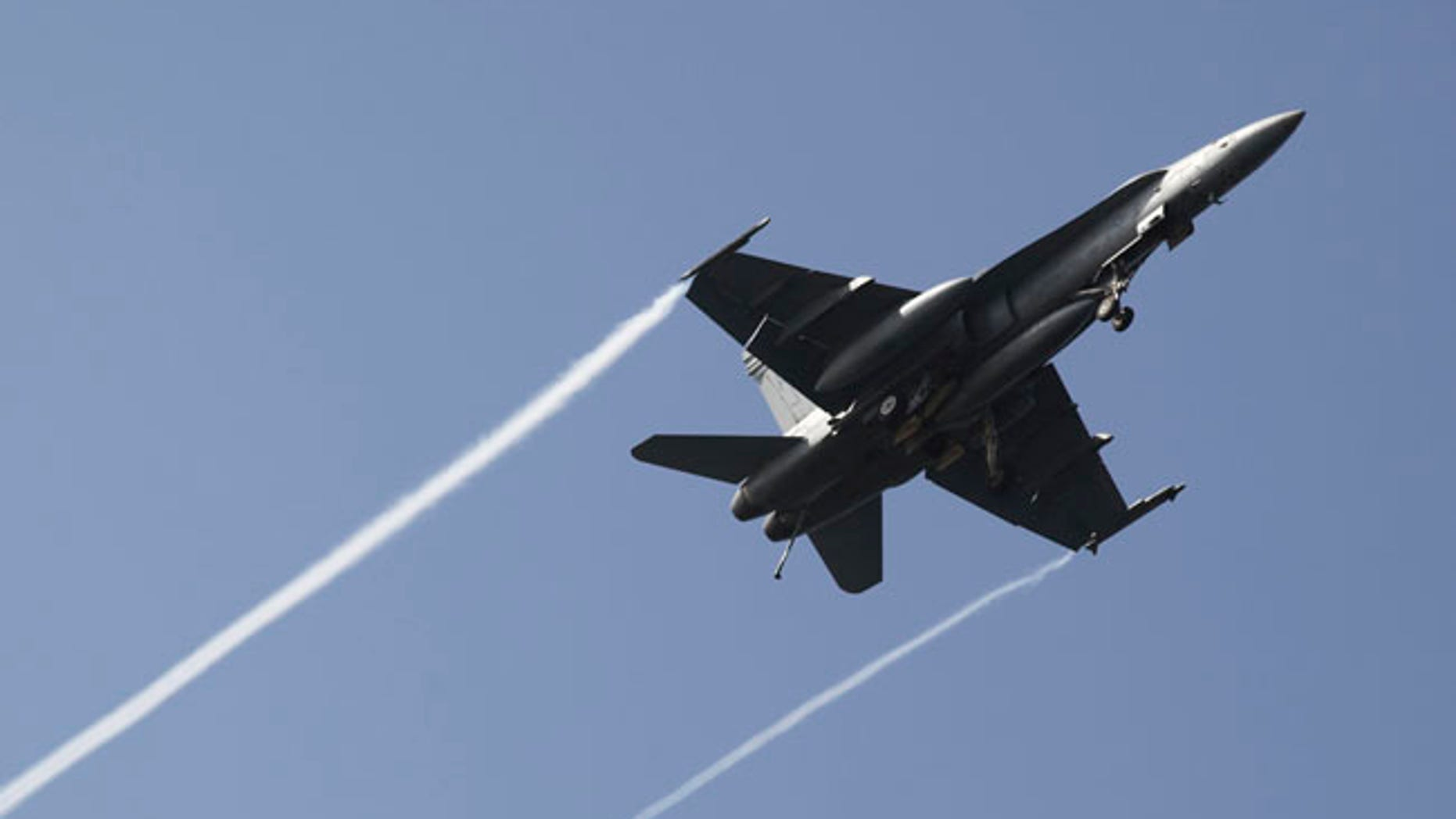 In this Monday, March 20, 2017 photograph, an F-18 fighter jet flies over the USS George H.W. Bush as the vessel travels toward the Strait of Hormuz. The arrival of the nuclear-powered aircraft carrier to the Persian Gulf marks the first such deployment under new U.S. President Donald Trump. (AP Photo/Jon Gambrell)