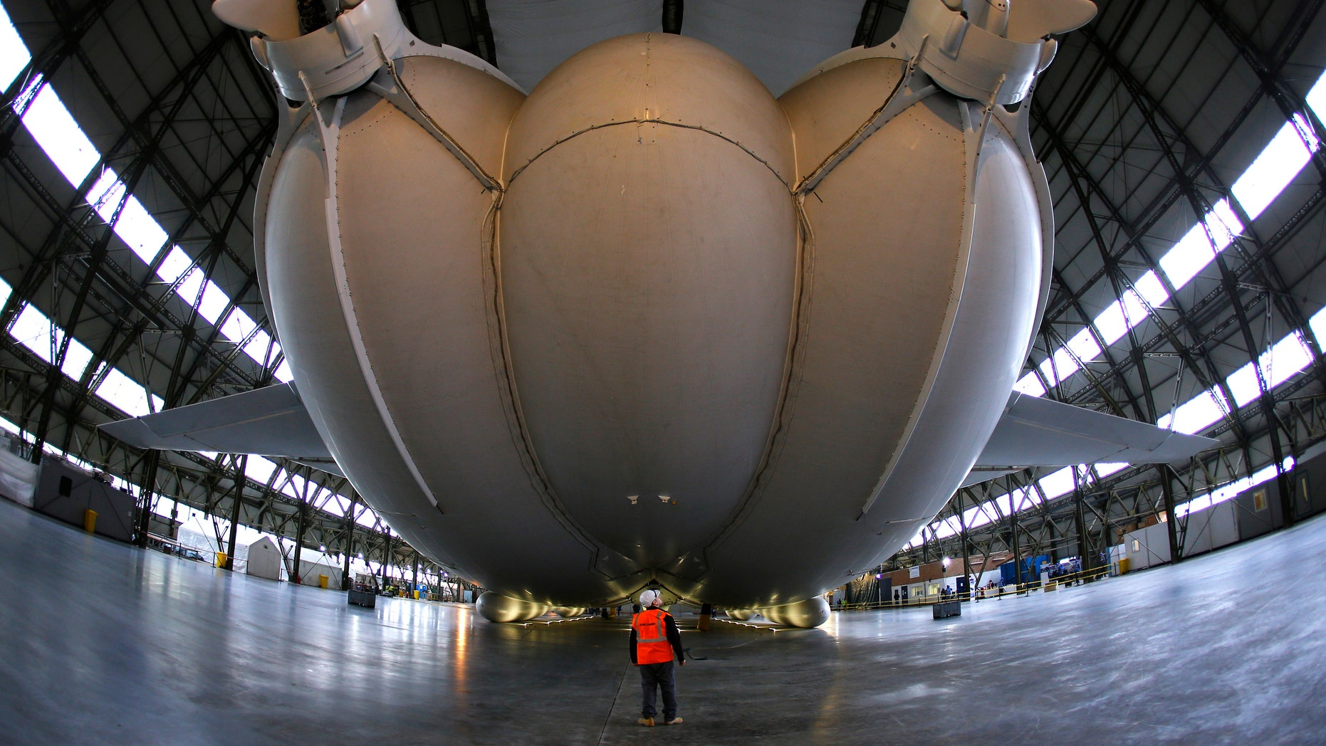 A worker stands under the Airlander 10 hybrid airship during its unveiling in Cardington, Britain March 21, 2016. (REUTERS/Darren Staples)
