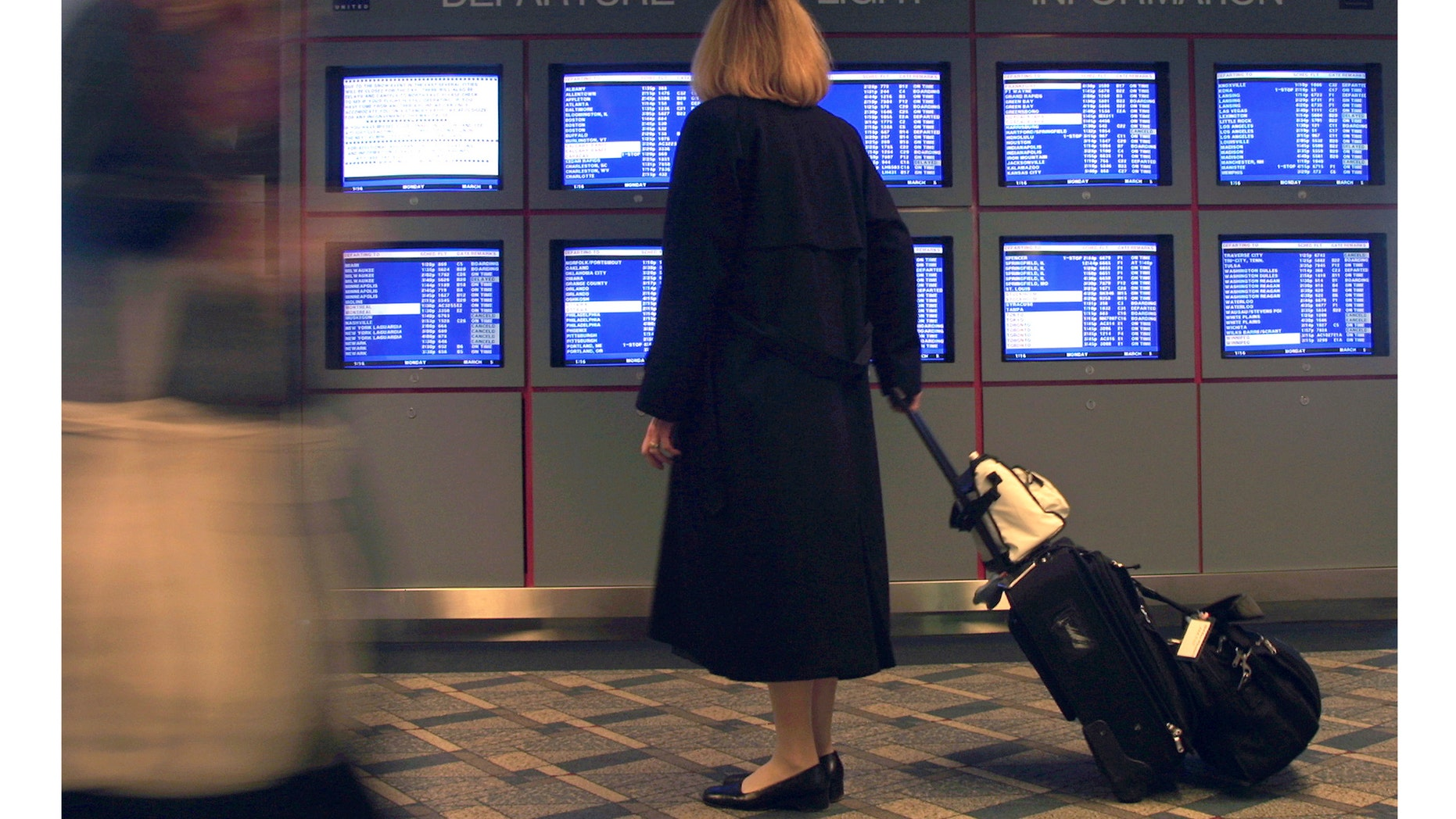 """386325 02: A United Airlines flight attendant stops to look at a departure flight information display March 5, 2001 at O''Hare International Airport in Chicago, IL. Hundreds of airline flights in and out of the Northeast United States were canceled as a """"Nor''easter"""" winter storm threatened to blast the region with snow and ice. (Photo by Tim Boyle/Newsmakers)"""