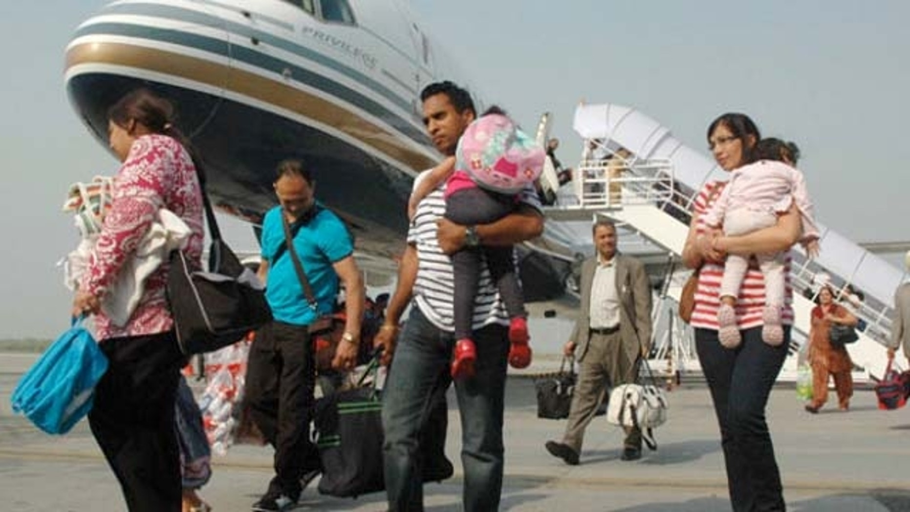 October 2, 2011: Indian passengers arrive from Austria at the Rajasansai International Airport on a Comtel Air flight in Amritsar.