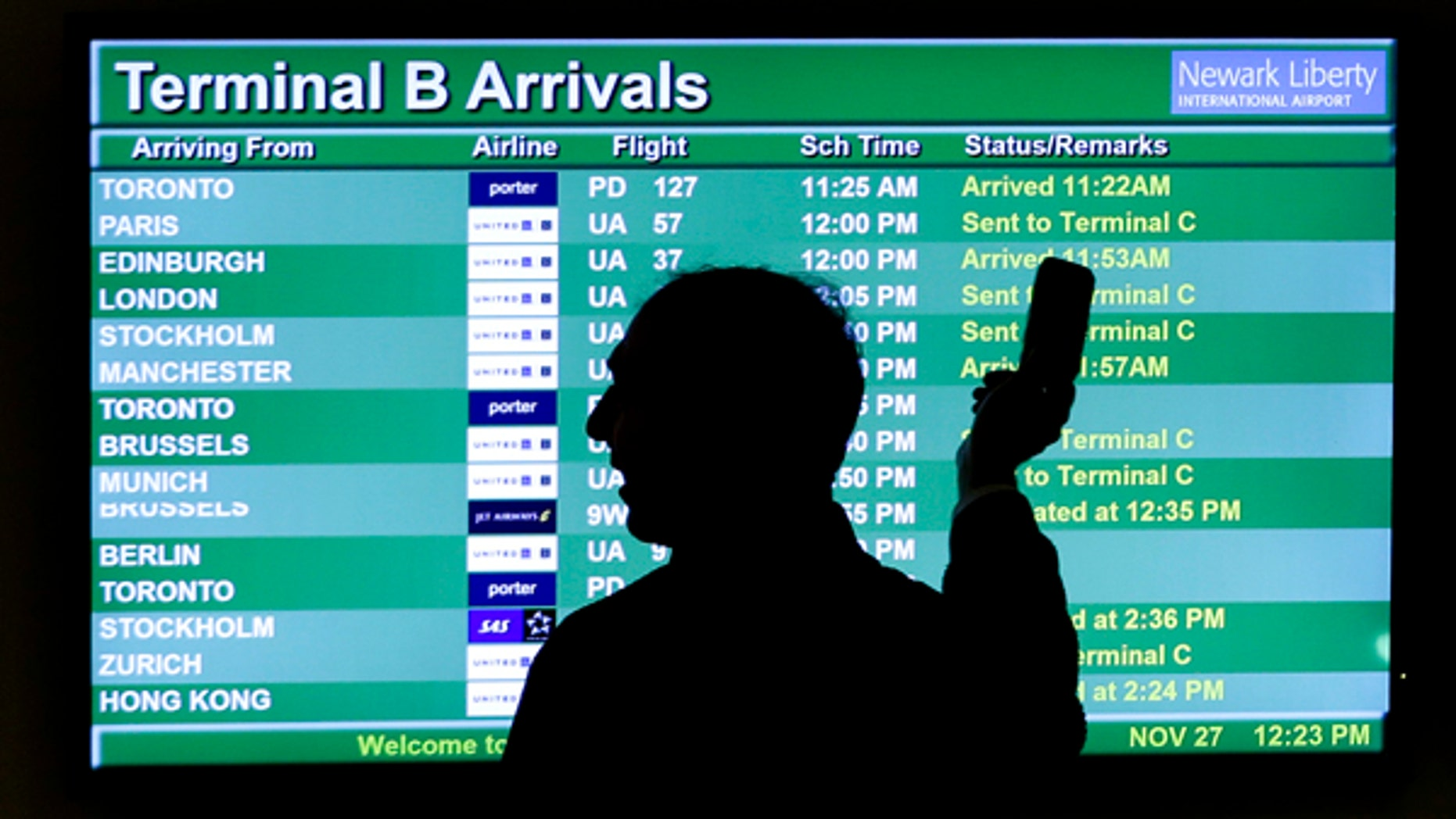 In this Wednesday, Nov. 27, 2013, file photo, a person points to a screen with an airplane travel list while holding up a phone at Newark Liberty International Airport, in Newark, N.J.