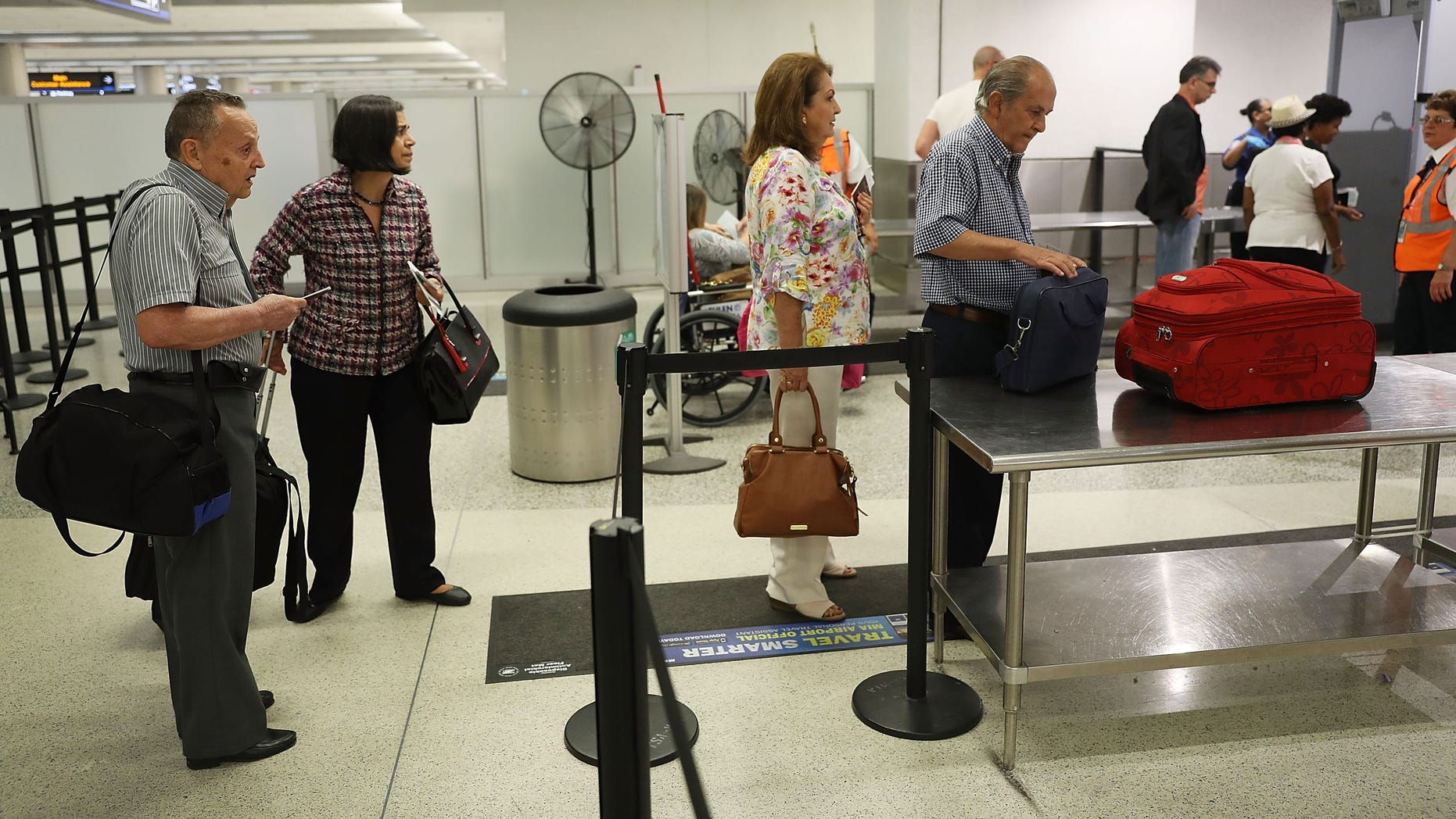 MIAMI, FL - JUNE 02:  Travelers go through the TSA PreCheck security point at Miami International Airport on June 2, 2016 in Miami, Florida. As the busy summer travel season heats up the Transportation Security Administration is encouraging people to sign up for the TSA PreCheck program to save time going through the airports security lines. Those enrolled in the program can leave their shoes, light outerwear and belt on during the terminal screening process as well as keeping their laptop in the carry-on suitcase without having to remove them at the checkpoint. (Photo by Joe Raedle/Getty Images)