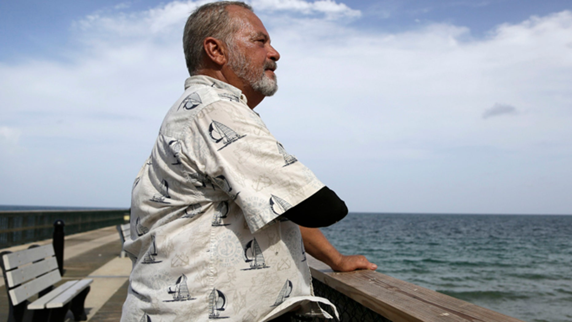 Aug. 5, 2015: Al Brennaka, 57, poses for a photograph in Pompano Beach, Fla. Brennaka lost half his arm at age 19 after being attacked by a shark while surfing off Daytona Beach.