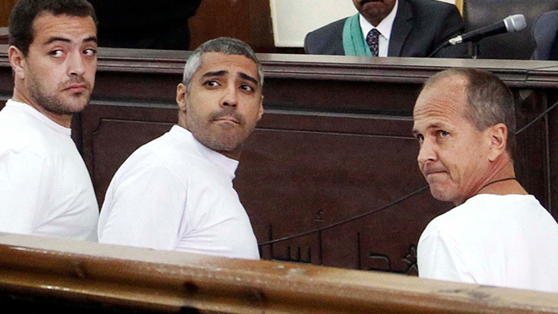 March 31, 2014: In this file photo, Al-Jazeera English producer Baher Mohamed, left, Canadian-Egyptian acting Cairo bureau chief Mohammed Fahmy, center, and correspondent Peter Greste, right, appear in court along with several other defendants during their trial on terror charges, in Cairo, Egypt. An Egyptian court on Monday, June 23, 2014, convicted three Al-Jazeera journalists and sentenced them to seven years in prison on terrorism-related charges after a trial dismissed by rights groups as a politically motivated sham. The verdict brought a landslide of international condemnation and calls for Egyptian President Abdel-Fattah el-Sissi to intervene. El-Sissi, on Tuesday said he will not interfere in court rulings, sparking an international outcry.
