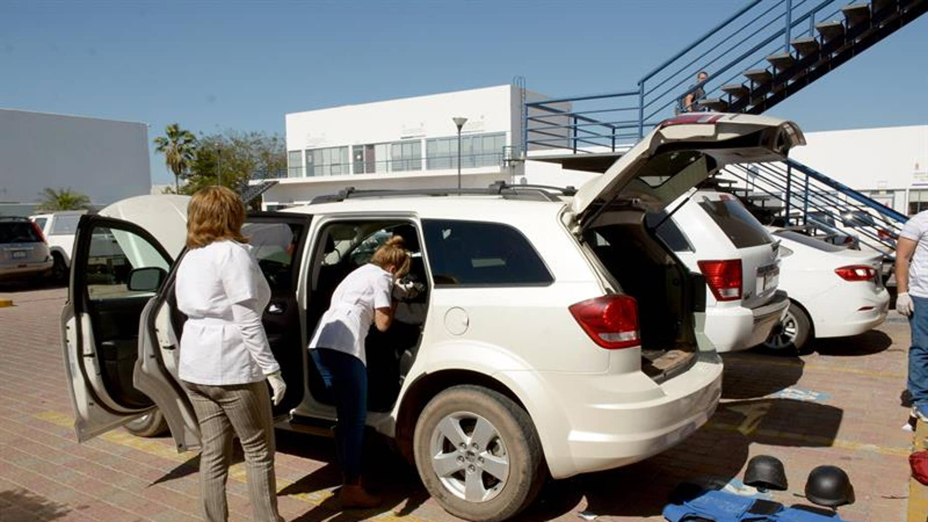 Mexican forensics inspect a vehicle of Al Jazeera TV Channel after being robbed in Novalato, Mexico, on March 29, 2017.