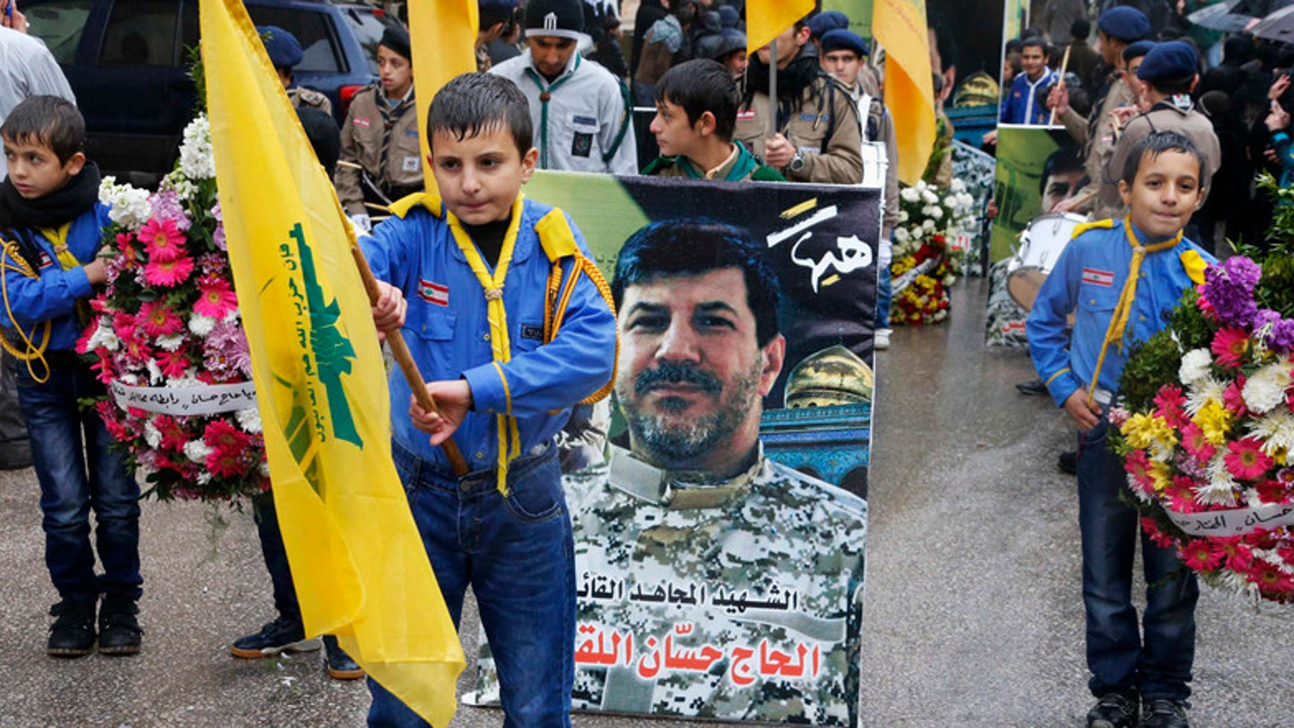 Hezbollah boy scouts carry the party flags and a picture of Hezbollah commander Hassan al-Lakkis during his funeral in Baalbeck, in Lebanon's Bekaa valley. (Reuters)