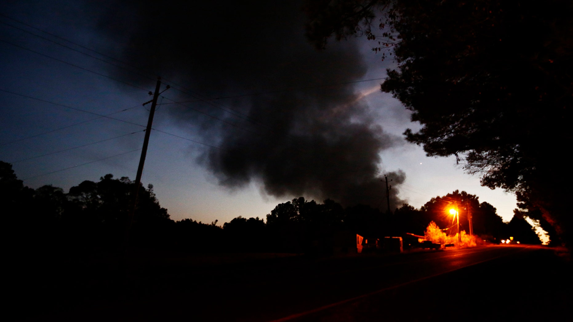 Light from a light pole shows a house near a plume of smoke from a Colonial Pipeline explosion, Monday, Oct. 31, 2016, in Helena, Ala.