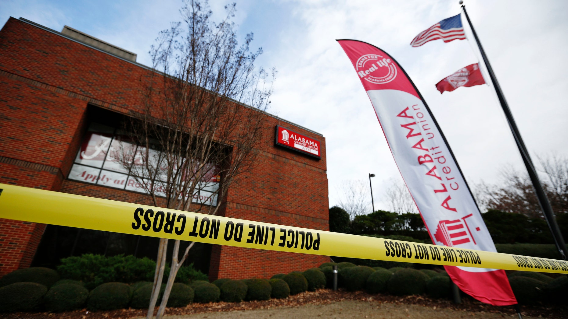 Police tape surrounds the Alabama Credit Union building after reports of a hostage standoff, Tuesday, Jan. 10, 2017, in Tuscaloosa, Ala. A group of hostages was freed, unharmed, and a man with a gun was arrested Tuesday at the credit union branch near the University of Alabama, police said. (AP Photo/Brynn Anderson)