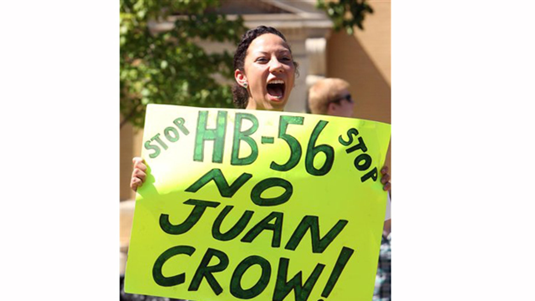 Ashley Hendricks, a University of Alabama student from Huntsville, holds a sign and chants while protesting HB-56 on Wednesday, Sept. 28, 2011. Approximately 40 students gathered for a protest of the immigration bill on the University of Alabama campus in Tuscaloosa, Ala.   (AP Photo/Tuscaloosa News, Robert Sutton)