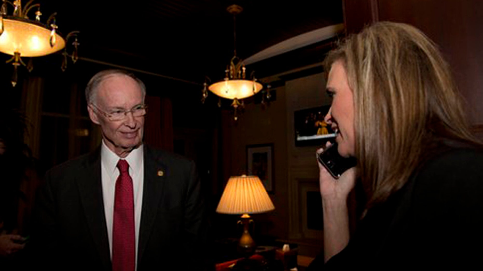 In this Tuesday, Nov. 4, 2014 file photo, Republican Gov. Robert Bentley listens to a phone call as Rebekah Mason, right, announces his win for Alabama governor, in Montgomery, Ala.