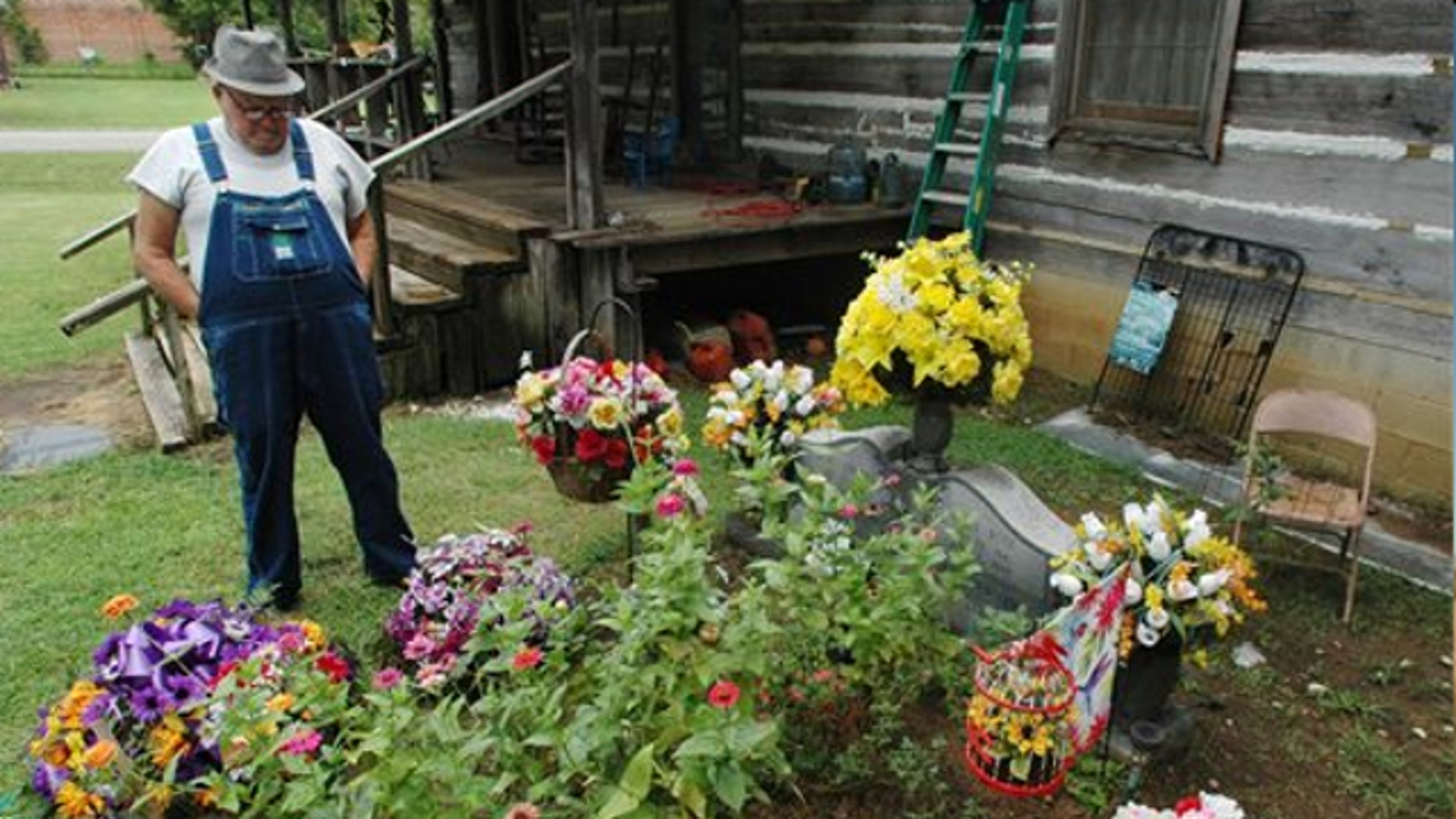 Aug. 10, 2012: James Davis, 73, stands over the grave of his wife, Patsy, in the front yard of the home they shared in Stevenson, Ala.