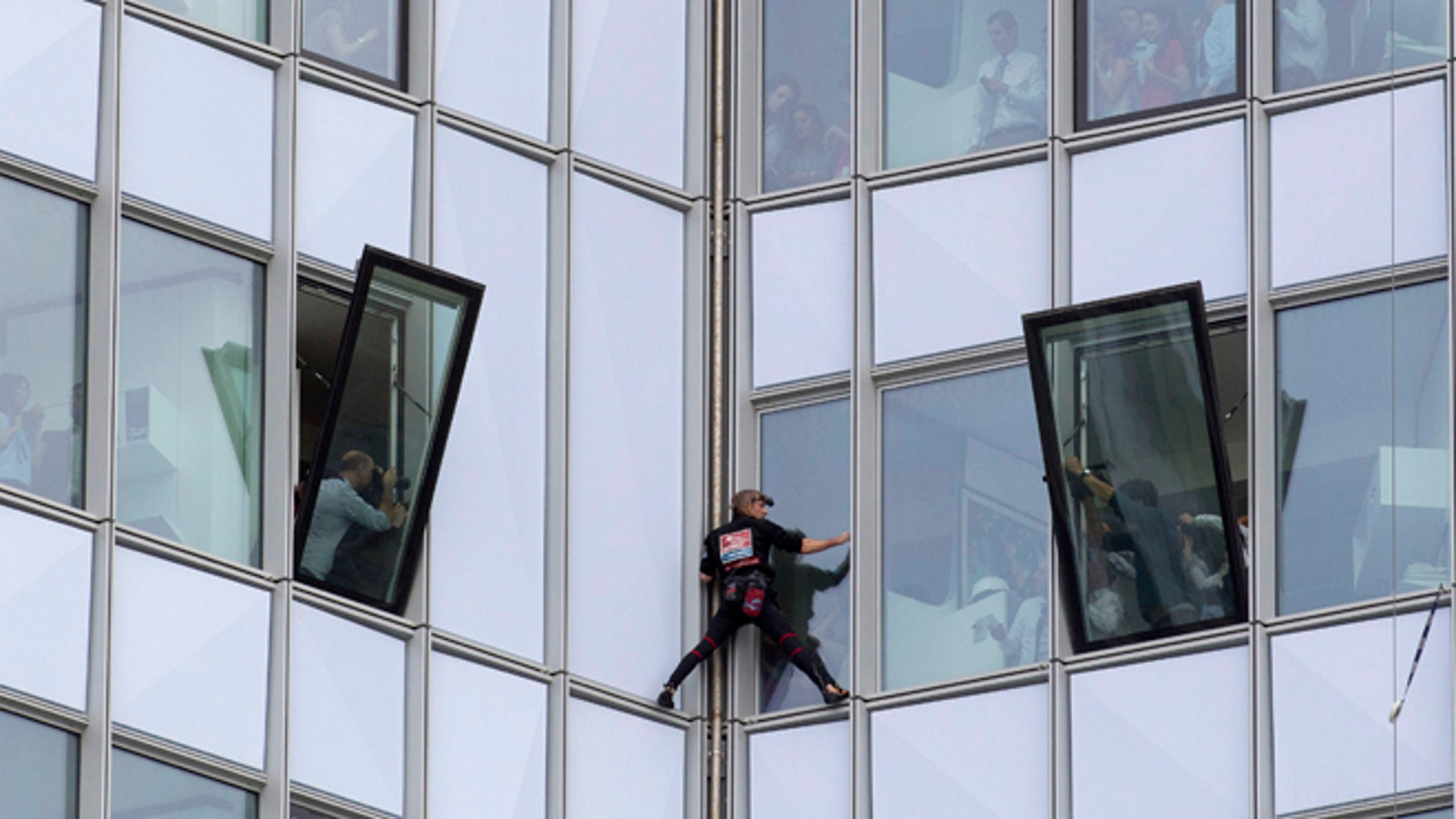 May 10, 2012: People look out of their windows as French urban climber Alain Robert, known as 'Spiderman', climbs up the 758 feet high First Tower, the tallest skyscraper in France, outside Paris.