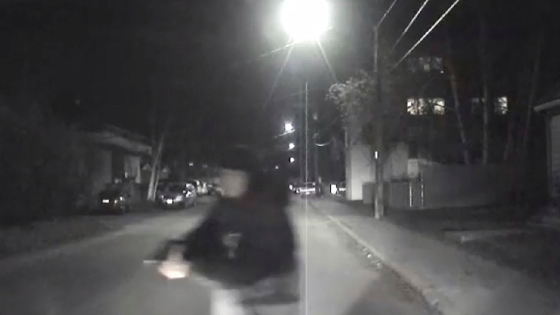 An image from video provided by the Fairbanks Police Department shows shows the suspect police believe abandoned a police car he stole after he shot an officer in Fairbanks, Ak., early Sunday, Oct. 16, 2016.