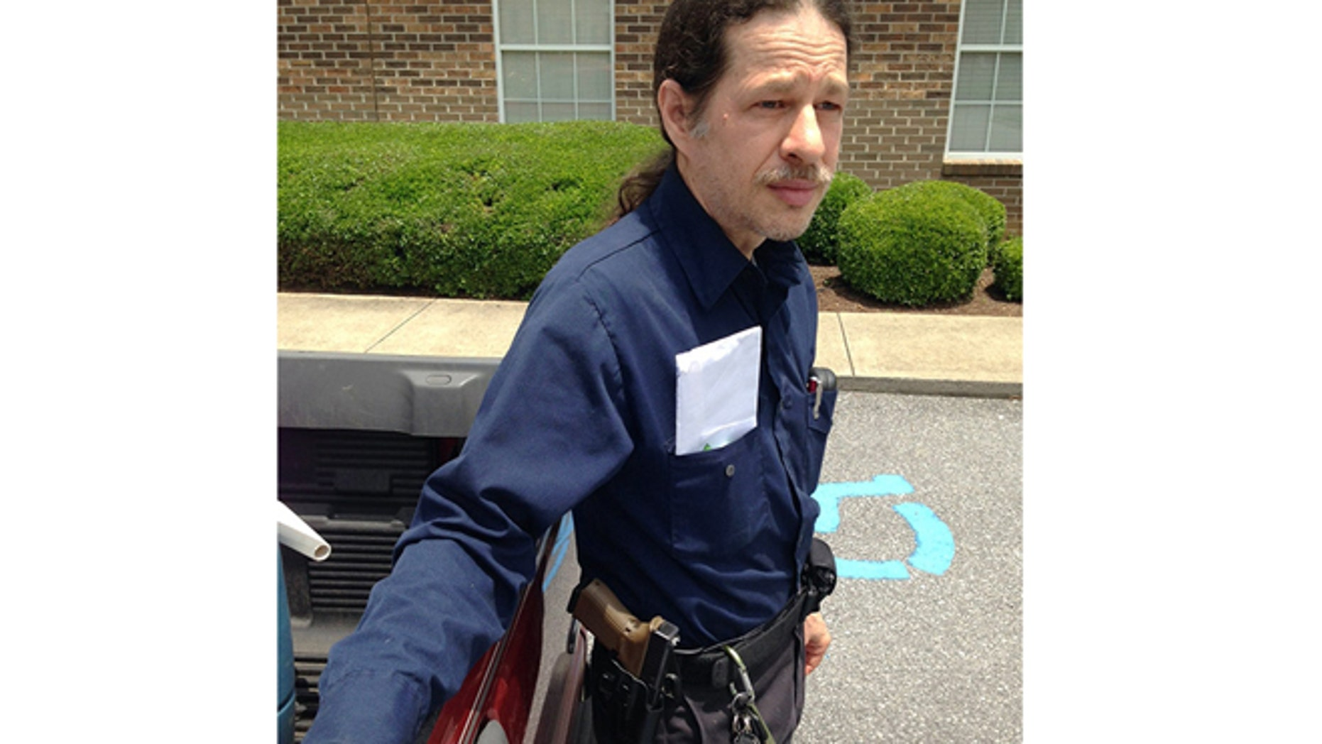 June 3, 2014: Gun rights activist John David Murphy stands outside his voting precinct with his firearm in Alabaster, Ala.