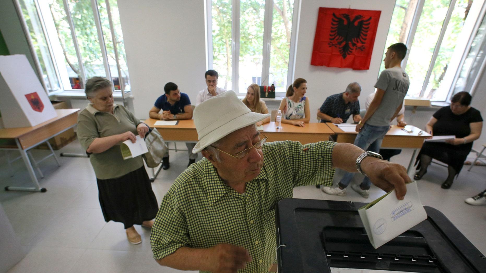 An Albanian man casts his ballot at a polling station in Tirana, Sunday, June 25, 2017.