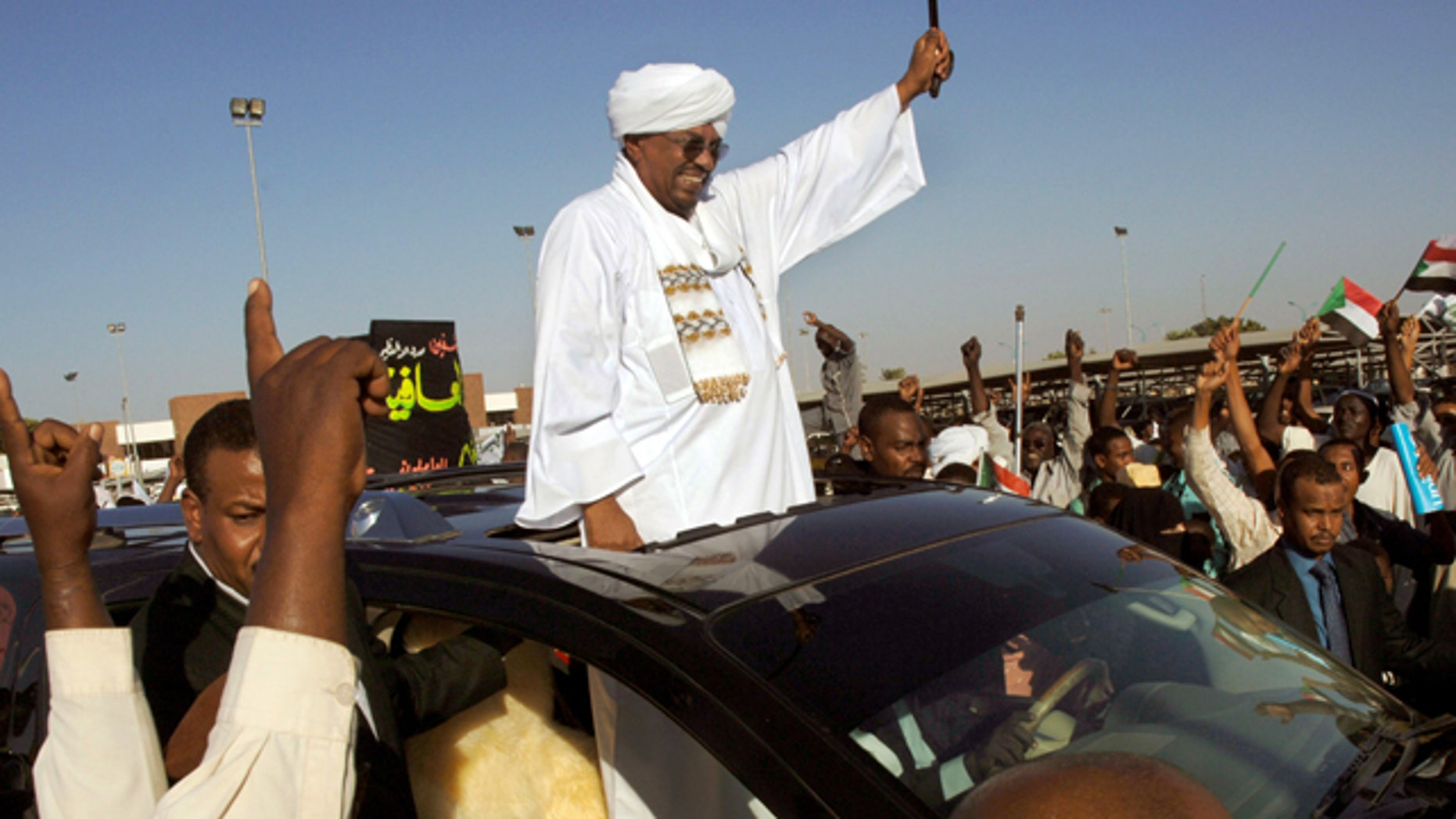 Nov. 14, 2012: Sudanese President Omar al-Bashir waves to people after his arrival at the Khartoum airport in Sudan.  Sudanese state television says al-Bashir has returned to the country after undergoing surgery in Saudi Arabia. (AP)