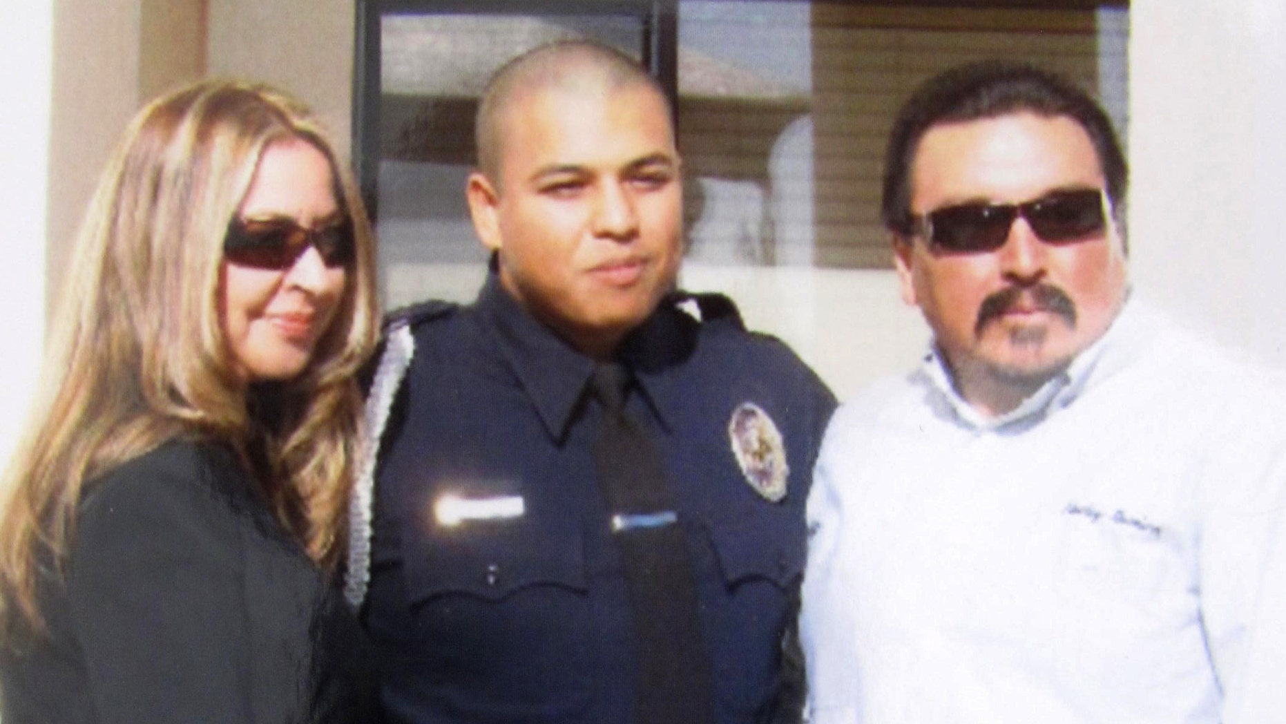 Officer Albert Covarrubias Jr. flanked by his father, Albert Sr., and his step-mother, Chela, on the day four years ago that he graduated from the police academy.