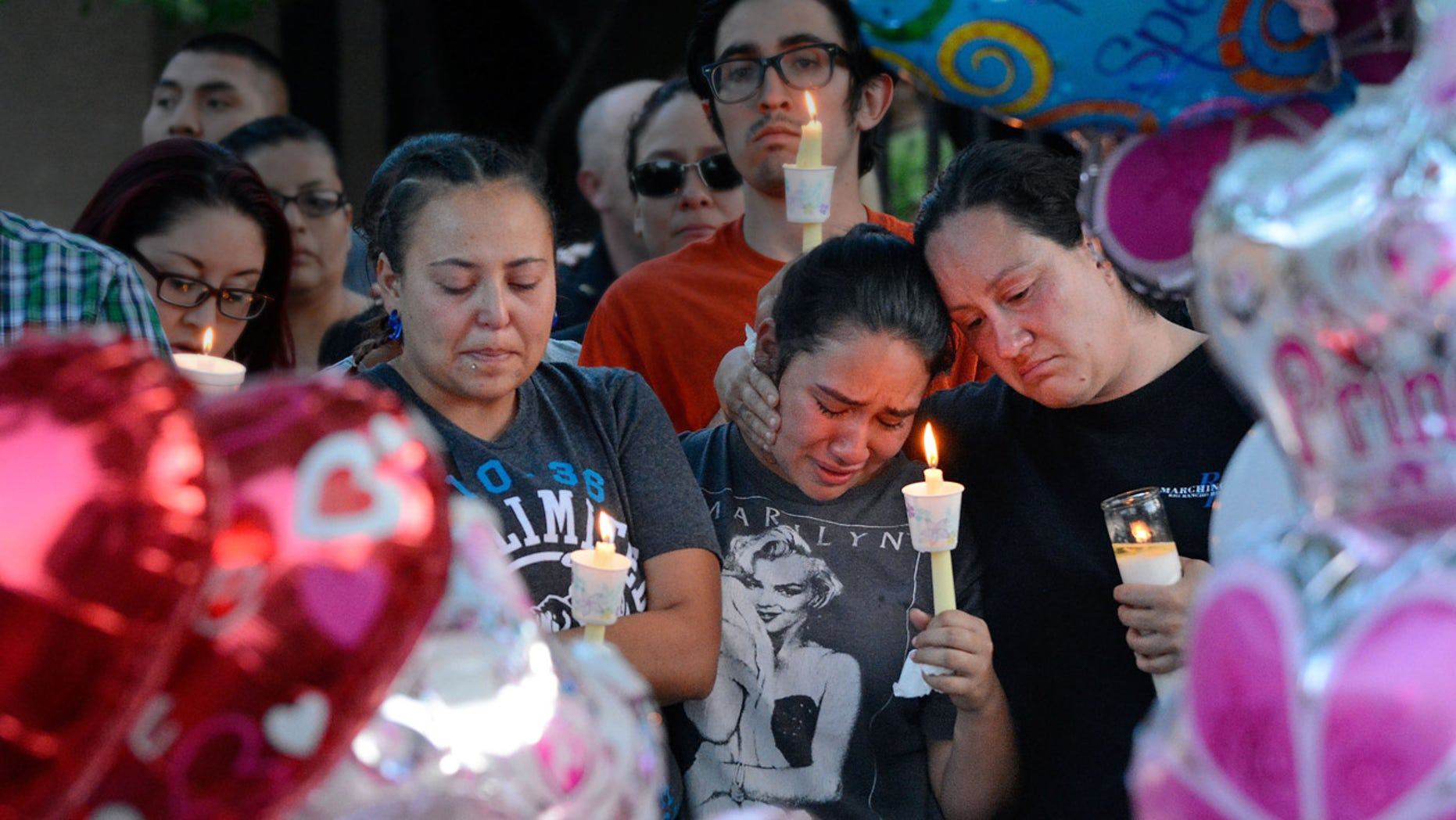 Aug. 25, 2016: Nicole Maldonado, Myriah Flores, and her mother Sharlene Benavidez attend a candlelight vigil for 10-year-old Victoria Martens at the apartment complex, in Albuquerque, N.M., where the young girl lived and was killed.