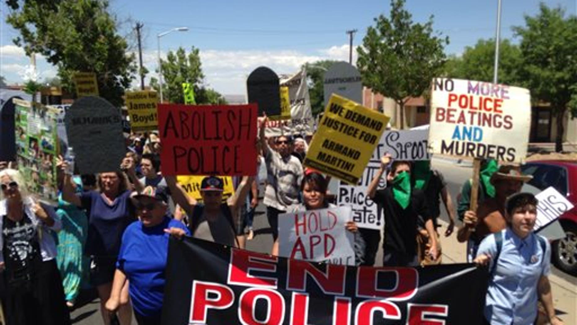 In this photo courtesy of David Correia, protesters march in a rally on Saturday, June 21, 2014 in Albuquerque, N.M. Critics of the Albuquerque Police Department say the march is aimed at pushing for drastic changes within Albuquerque police following a harsh U.S. Justice Department report over the agencys use of force. (AP Photo/Courtesy of David Correia)