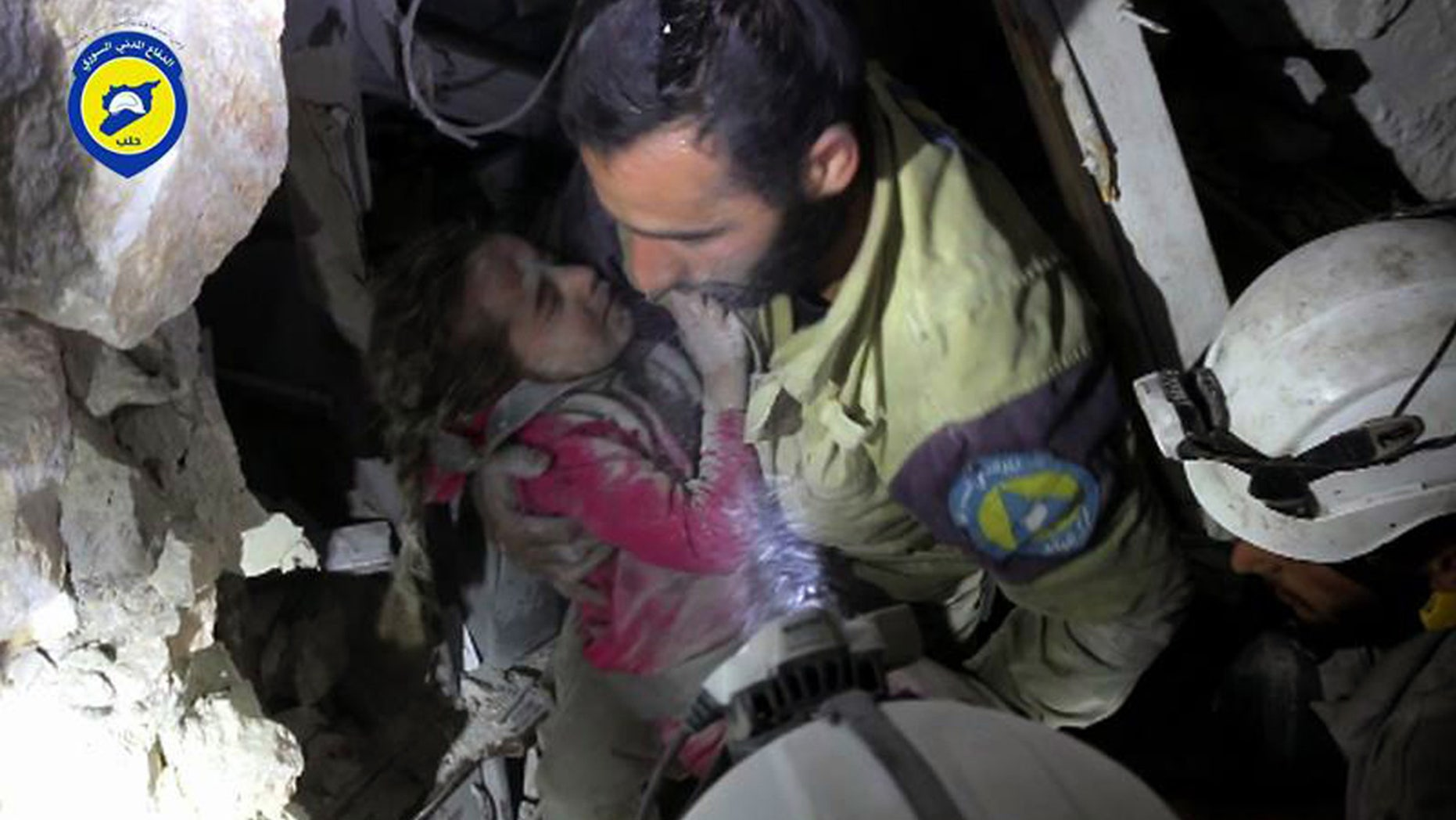 Sept. 28, 2016: This photo provided by the Syrian Civil Defense group known as the White Helmets shows a Civil Defense worker carrying Ghazal Akhtarini from under the rubble after airstrikes hit the al-Shaar neighborhood in Aleppo, Syria.