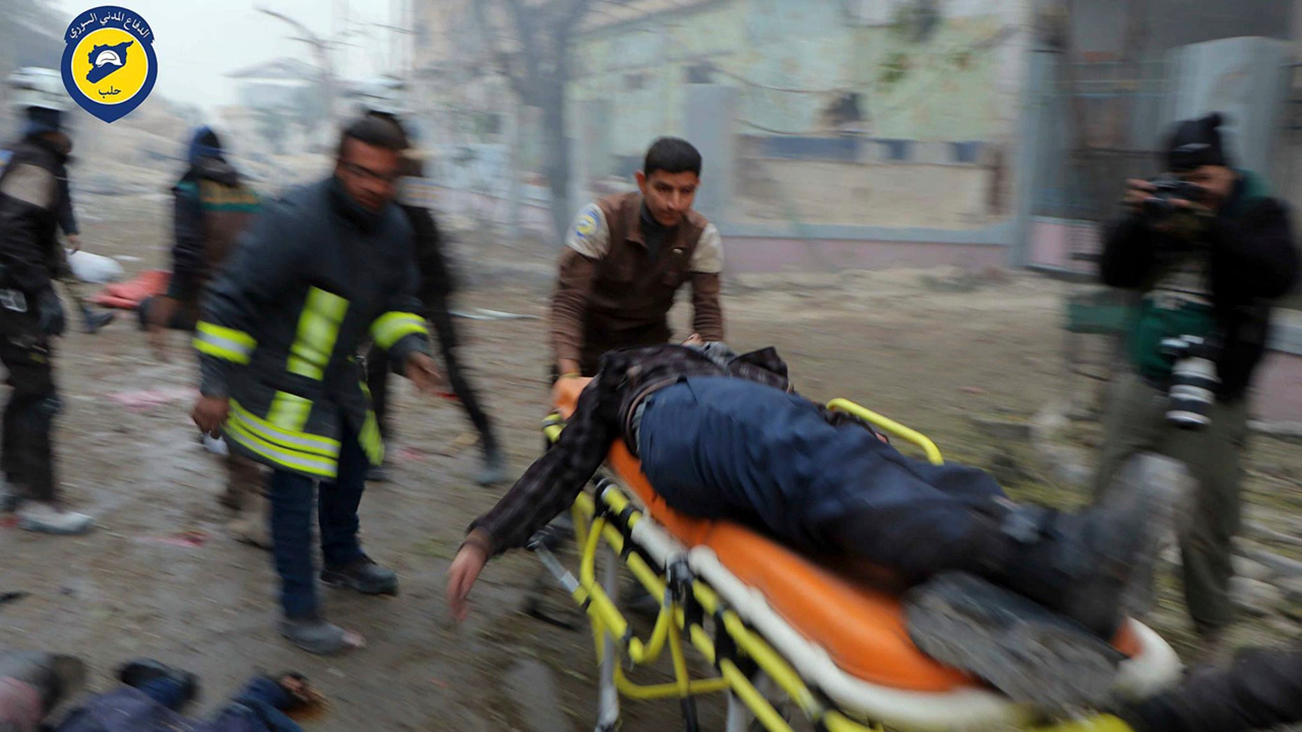 Nov. 30, 2016: This photo provided by the Syrian Civil Defense White Helmets, which has been authenticated based on its contents and other AP reporting, shows Civil Defense workers carrying a victim on a stretcher after artillery fire struck the Jub al-Quba district in Aleppo.
