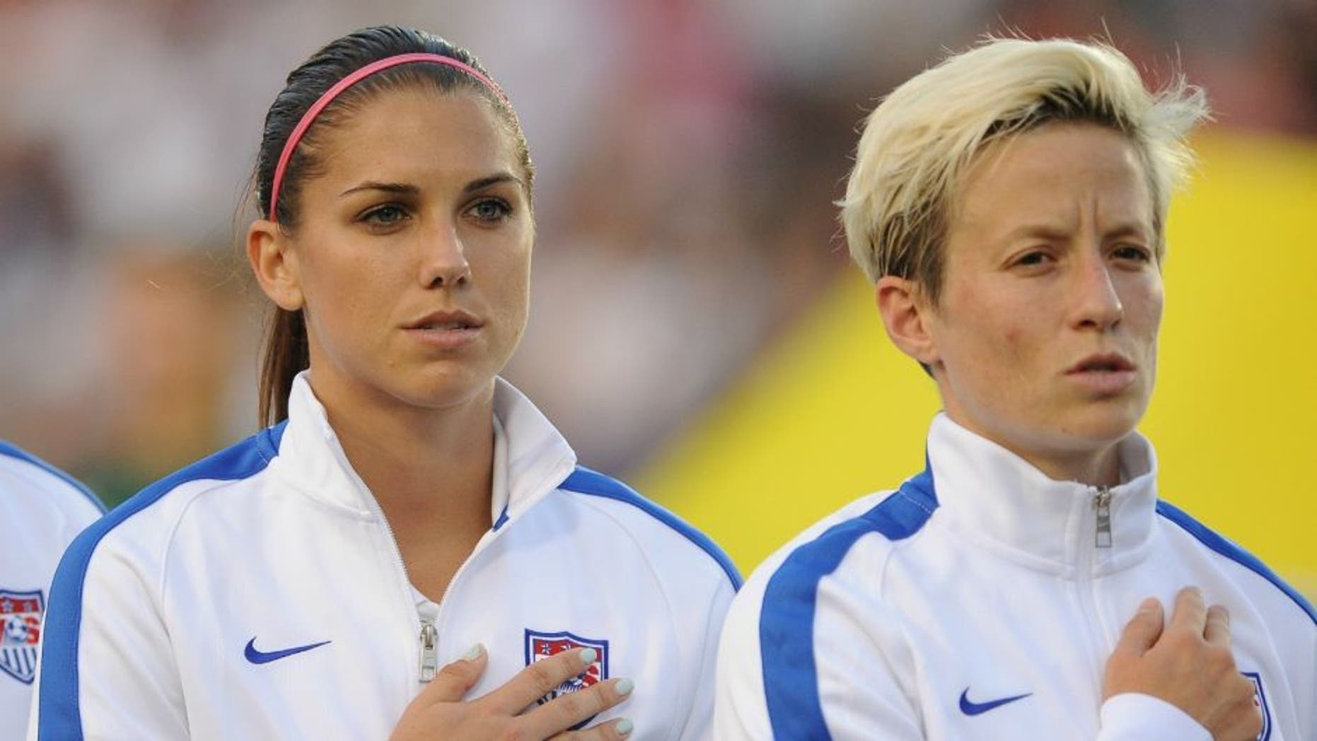 CARY, NC - AUGUST 20: Lauren Holiday #12, Alex Morgan #13 and Megan Rapinoe #15 of the U.S. women's national team stand at attention during the National Anthem prior to their match against the Swiss women's national team at WakeMed Soccer Park on August 20, 2014 in Cary, North Carolina. (Photo by Lance King/Getty Images)