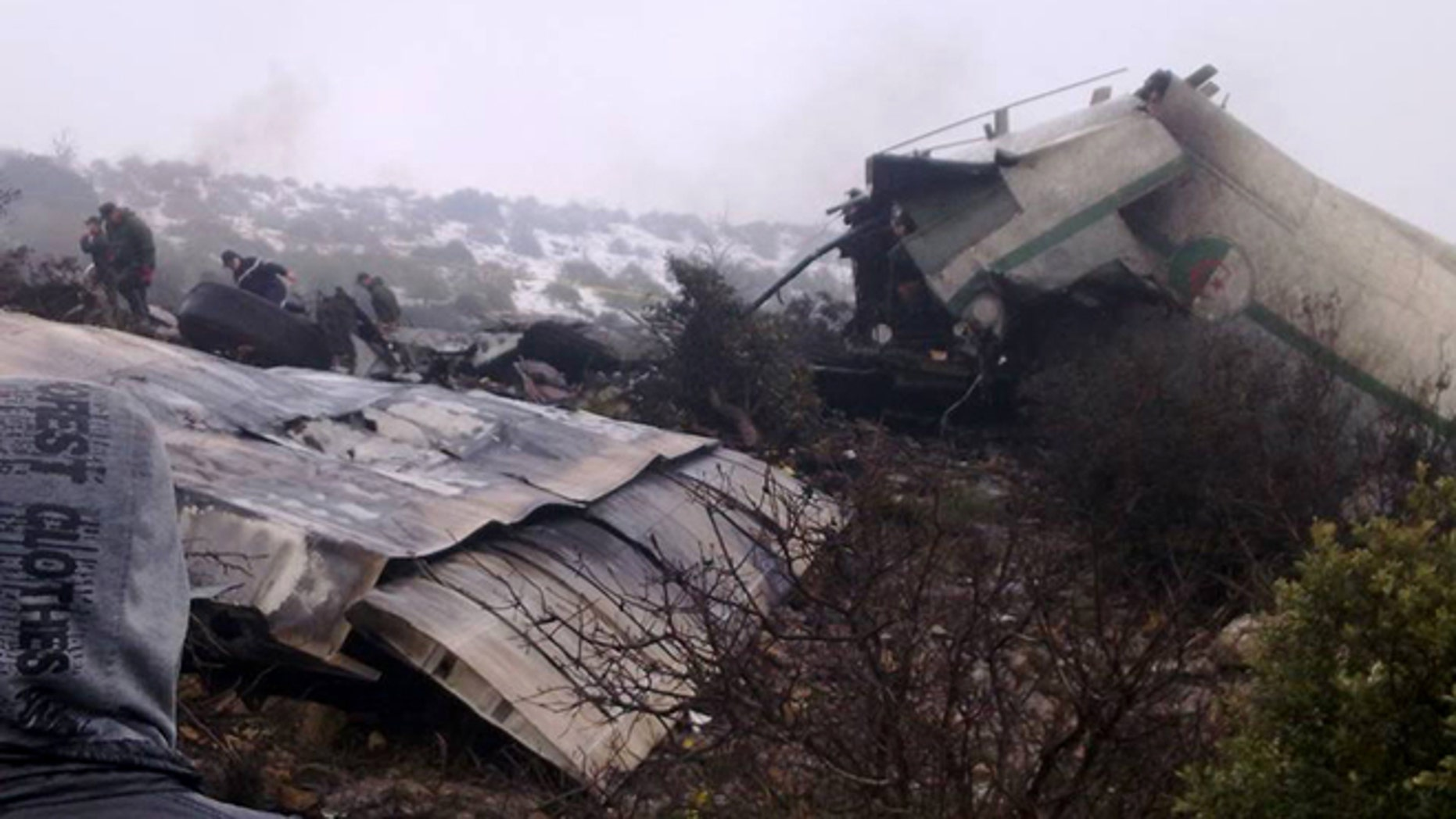 Feb. 11, 2014: A man watches rescue workers working at the wreckage of Algerian military transport aircraft after it slammed into a mountain in the country's rugged eastern region.