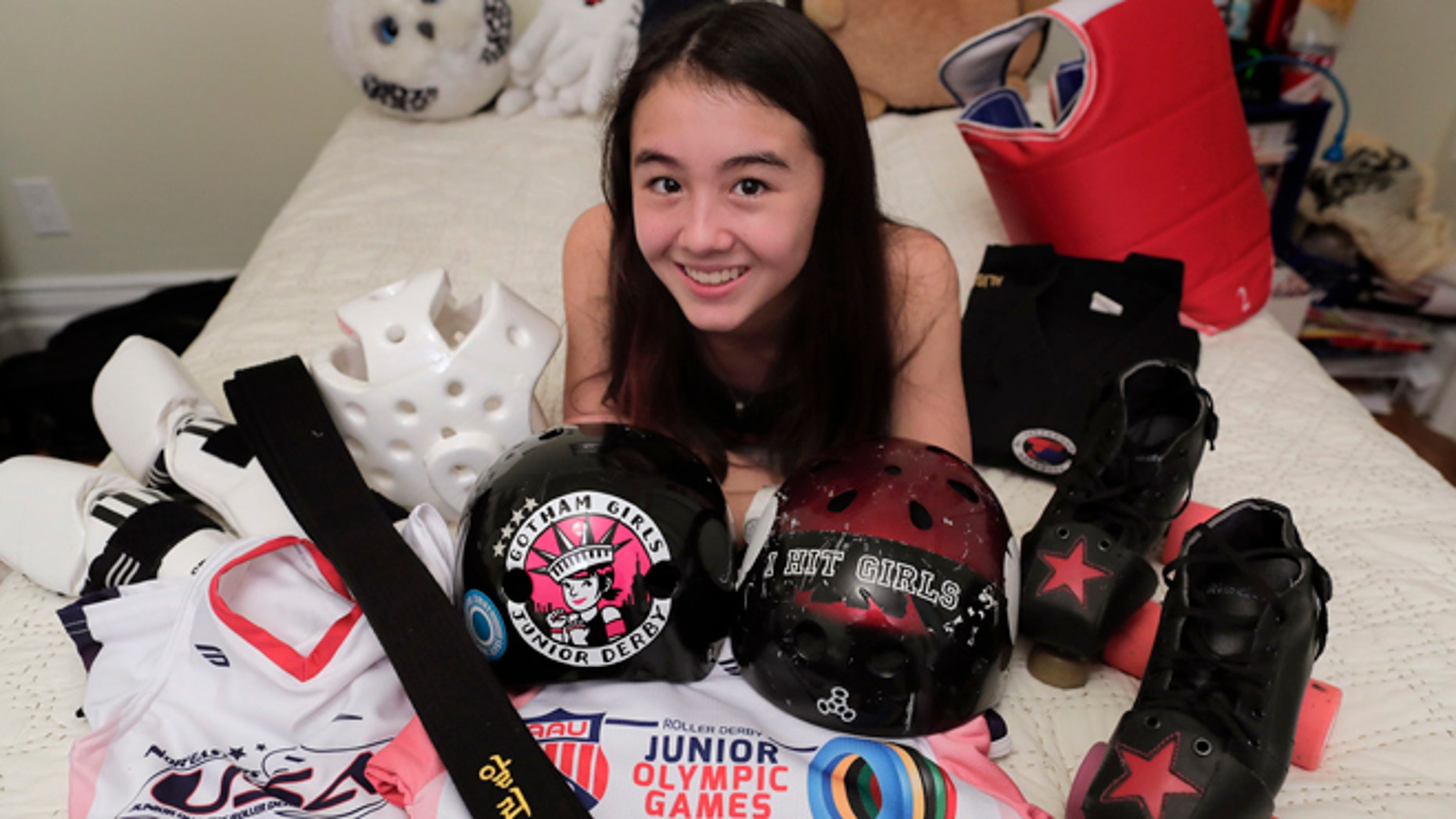 Alison Rogers poses for a photo with some of the jerseys and equipment she uses for the various sports she plays, including Tae Kwon Do and roller derby, at her home.