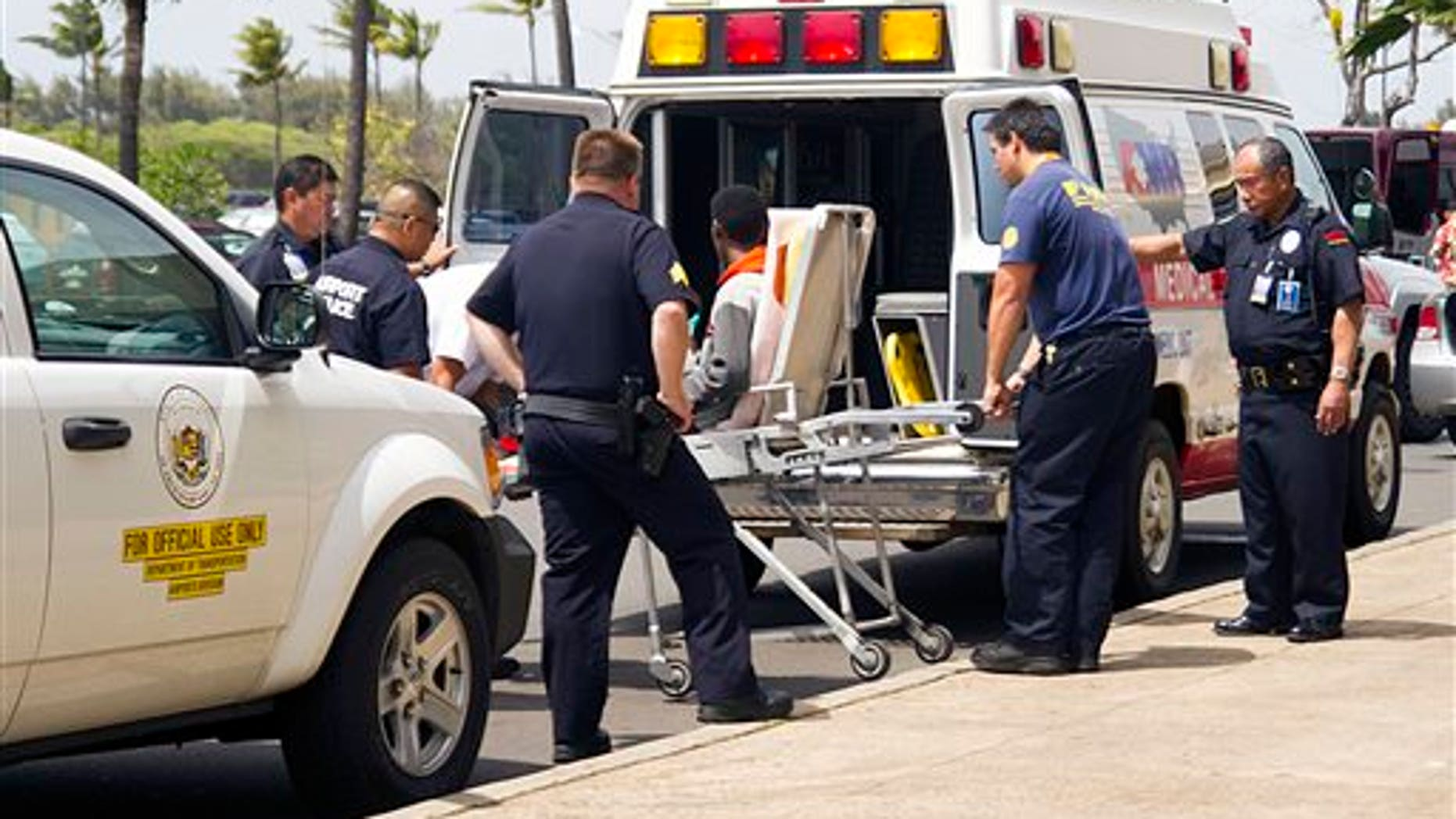 """A 16-year-old boy, seen sitting on a stretcher center, who stowed away in the wheel well of a flight from San Jose, Calif., to Maui is loaded into an ambulance at Kahului Airport in Kahului, Maui, Hawaii Sunday afternoon, April 20, 2014. The boy survived the trip halfway across the Pacific Ocean unharmed despite frigid temperatures at 38,000 feet and a lack of oxygen, FBI and airline officials said. FBI spokesman Tom Simon in Honolulu told The Associated Press on Sunday night that the boy was questioned by the FBI after being discovered on the tarmac at the Maui airport with no identification. """"Kid's lucky to be alive,"""" Simon said. (AP Photo/The Maui News, Chris Sugidono)"""