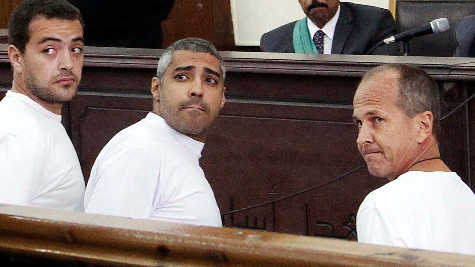 March 31, 2014:  Al-Jazeera English producer Baher Mohamed, left, Canadian-Egyptian acting Cairo bureau chief Mohammed Fahmy, center, and correspondent Peter Greste, right, appear in court along with several other defendants during their trial on terror charges, in Cairo