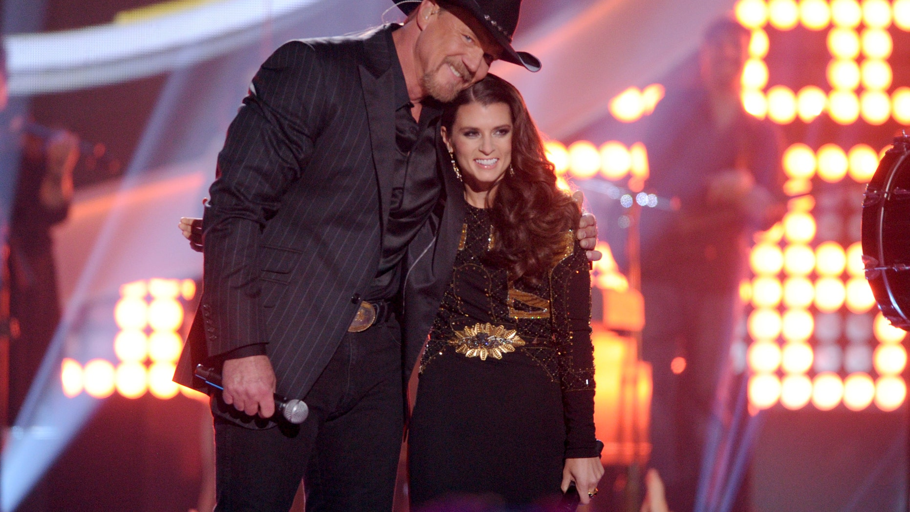 Trace Adkins, left, and Danica Patrick speak on stage at the American Country Awards at the Mandalay Bay Resort & Casino on Tuesday, Dec. 10, 2013, in Las Vegas.