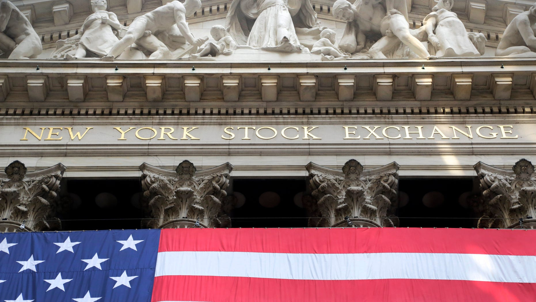 FILE -- July 6, 2015:  An American flag is draped on the exterior of the New York Stock Exchange.  (AP Photo/Mark Lennihan)
