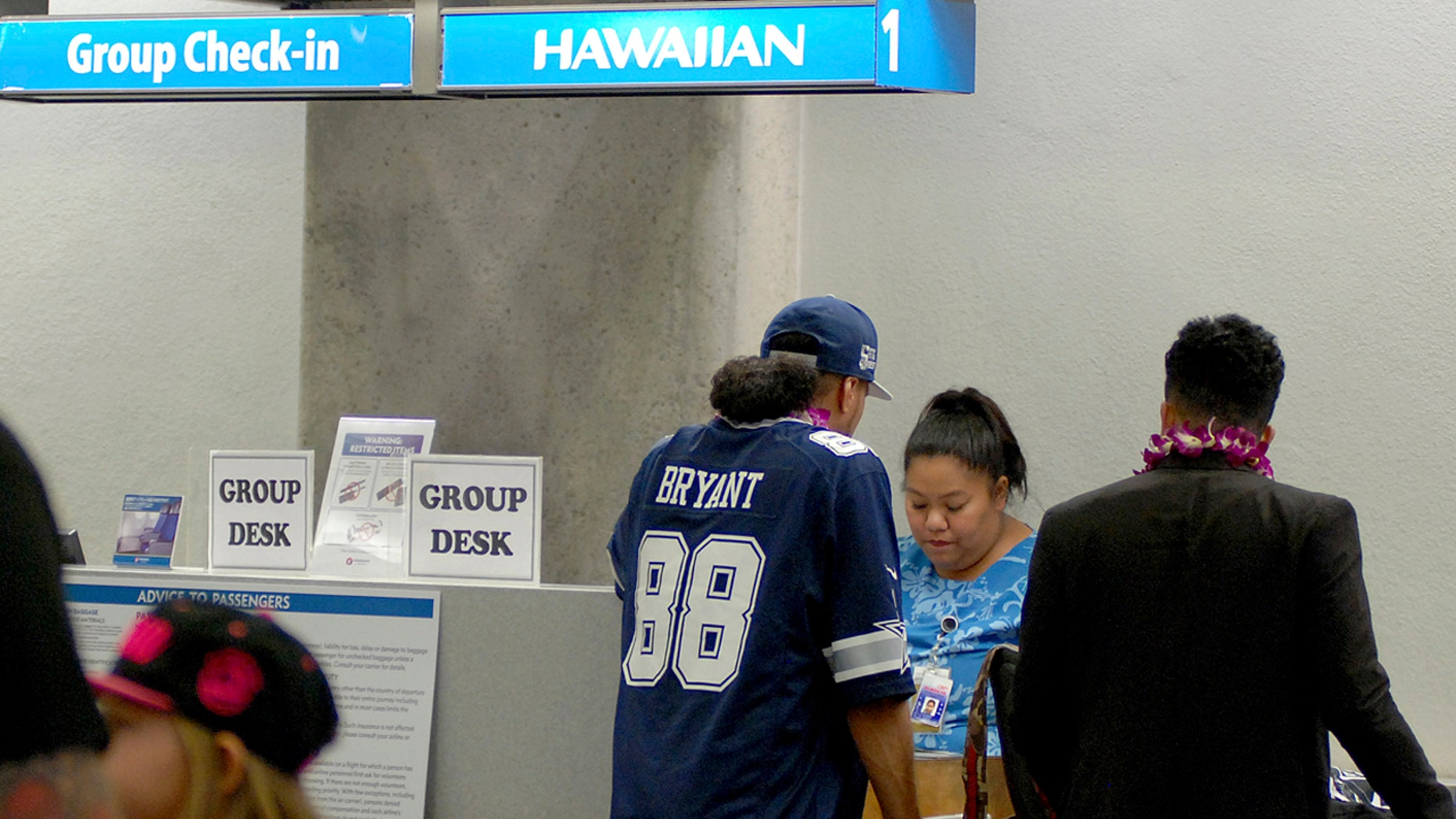 In this Oct. 10, 2016 photo, passengers stand at a Hawaiian Airlines check-in counter before a flight to Pago Pago, American Samoa at Honolulu International Airport in Honolulu.