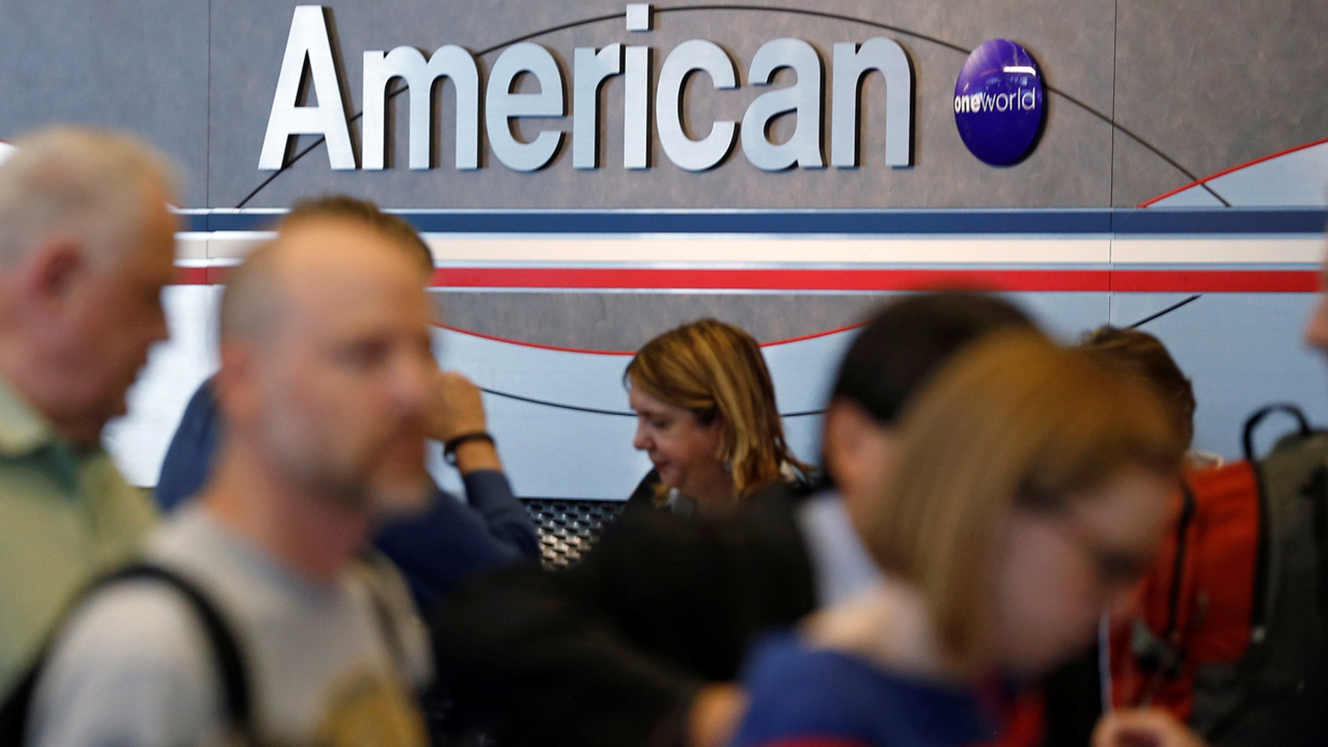Travelers line up at an American Airlines ticket counter at O'Hare Airport in Chicago, Illinois, May 13, 2014.
