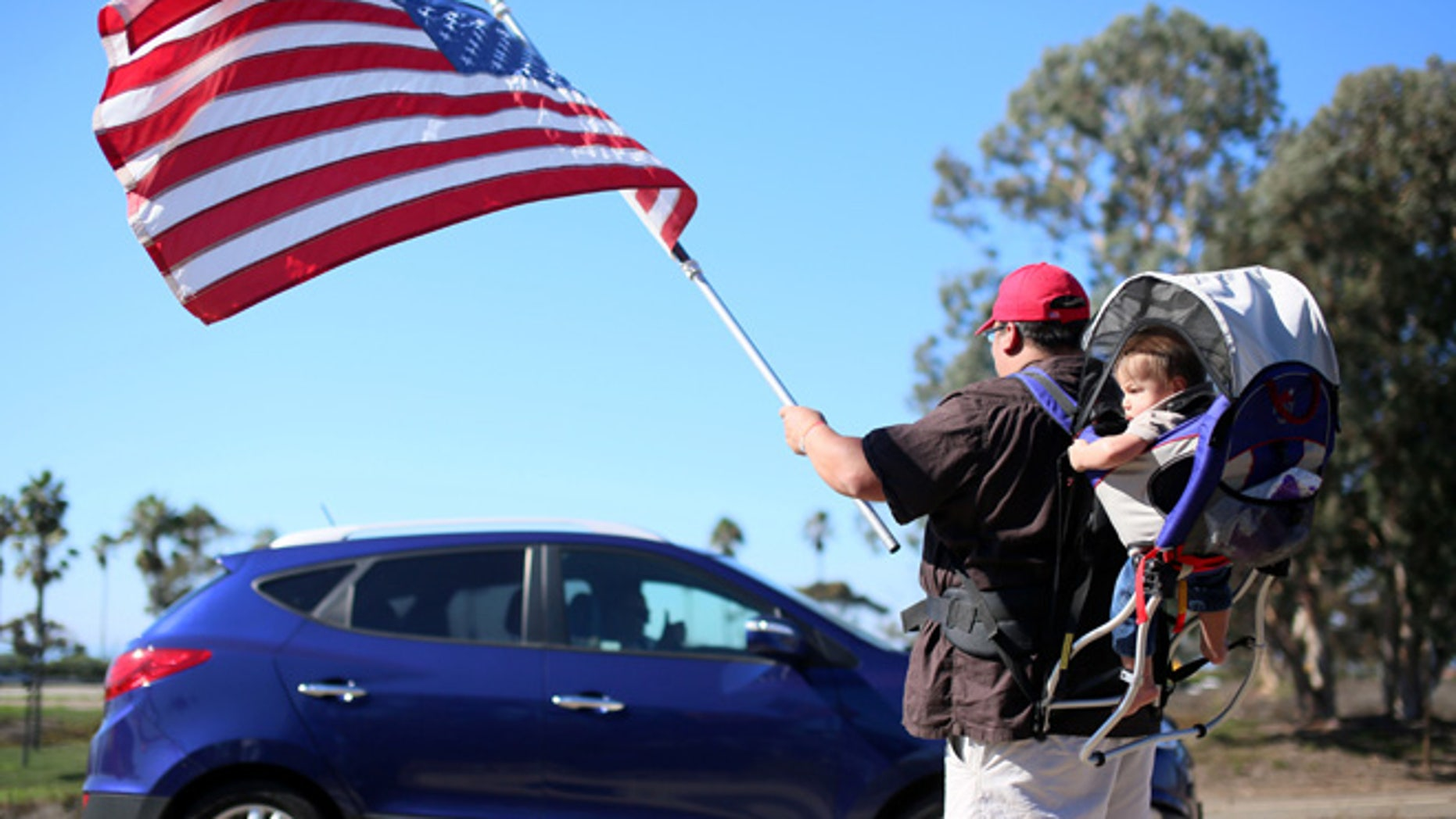 Demonstrator Steven Morales with his son Steven Jr. waves an American flag for motorists in support of President elect Donald Trump outside of Camp Pendleton in Oceanside, California, U.S. November 11, 2016.  REUTERS/Sandy Huffaker - RTX2TA95