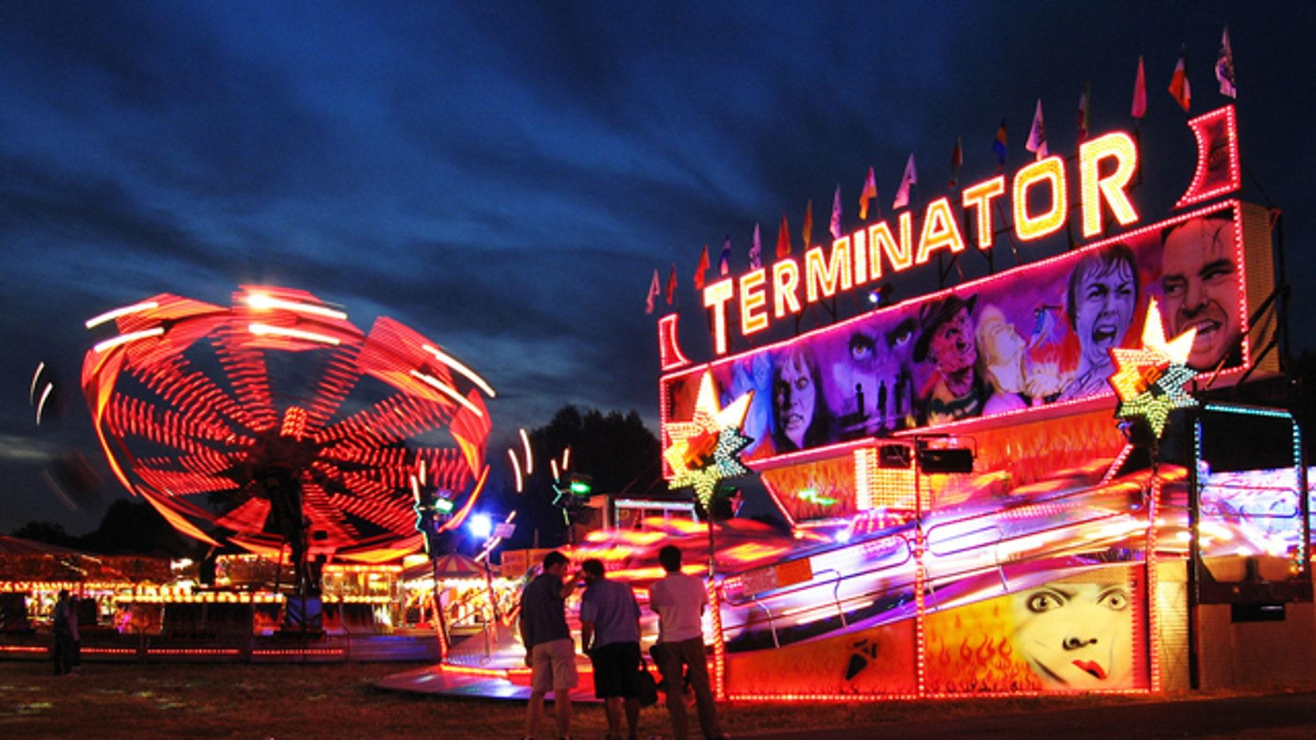 Rides glow at night at the Cambridge Midsummer Fair amusement park.