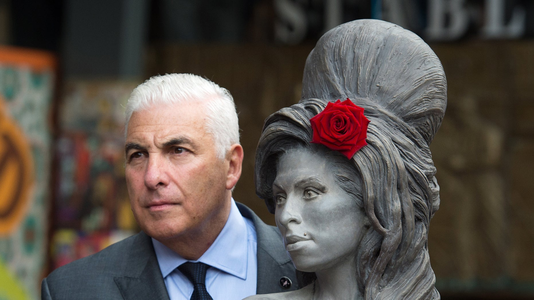 September 14, 2014. Mitch Winehouse poses for a picture with a statue of his late daughter, Amy Winehouse after it was unveiled in Camden's Stables Market, in London, England.