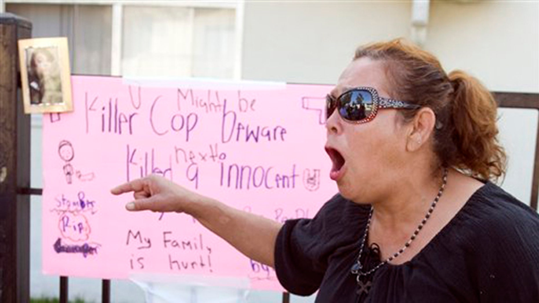 """July 23, 2012: Maria, who wouldn't give her last name because she said she fears the police, shouts """"no mas"""", at a memorial on Anna Drive in Anaheim, Calif. for Manuel Angel Diaz, 25, of Santa Ana."""