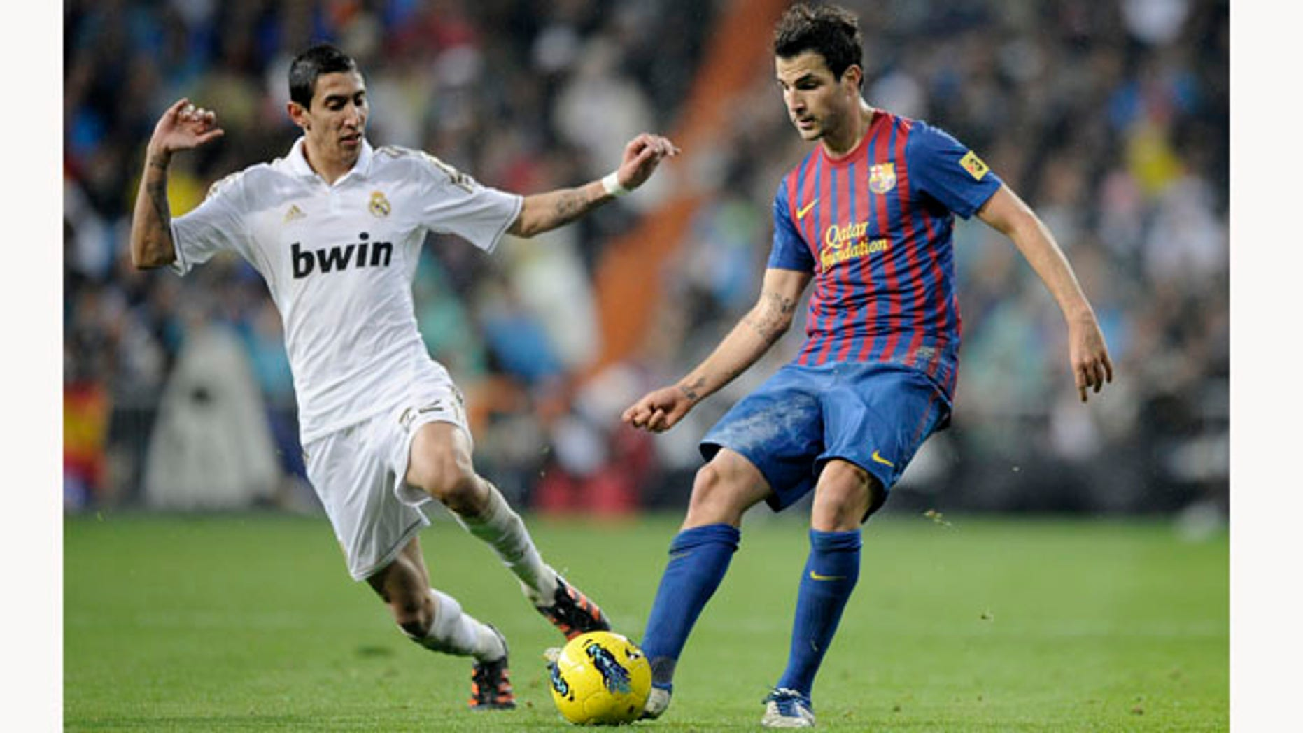 Real Madrid's Angel Di Maria from Argentina, left, duels for the ball with Barcelona's Cesc Fabregas, right, during their Spanish La Liga soccer match at the Santiago Bernabeu stadium, in Madrid, Saturday, Dec. 10, 2011. (AP Photo/Daniel Ochoa de Olza)