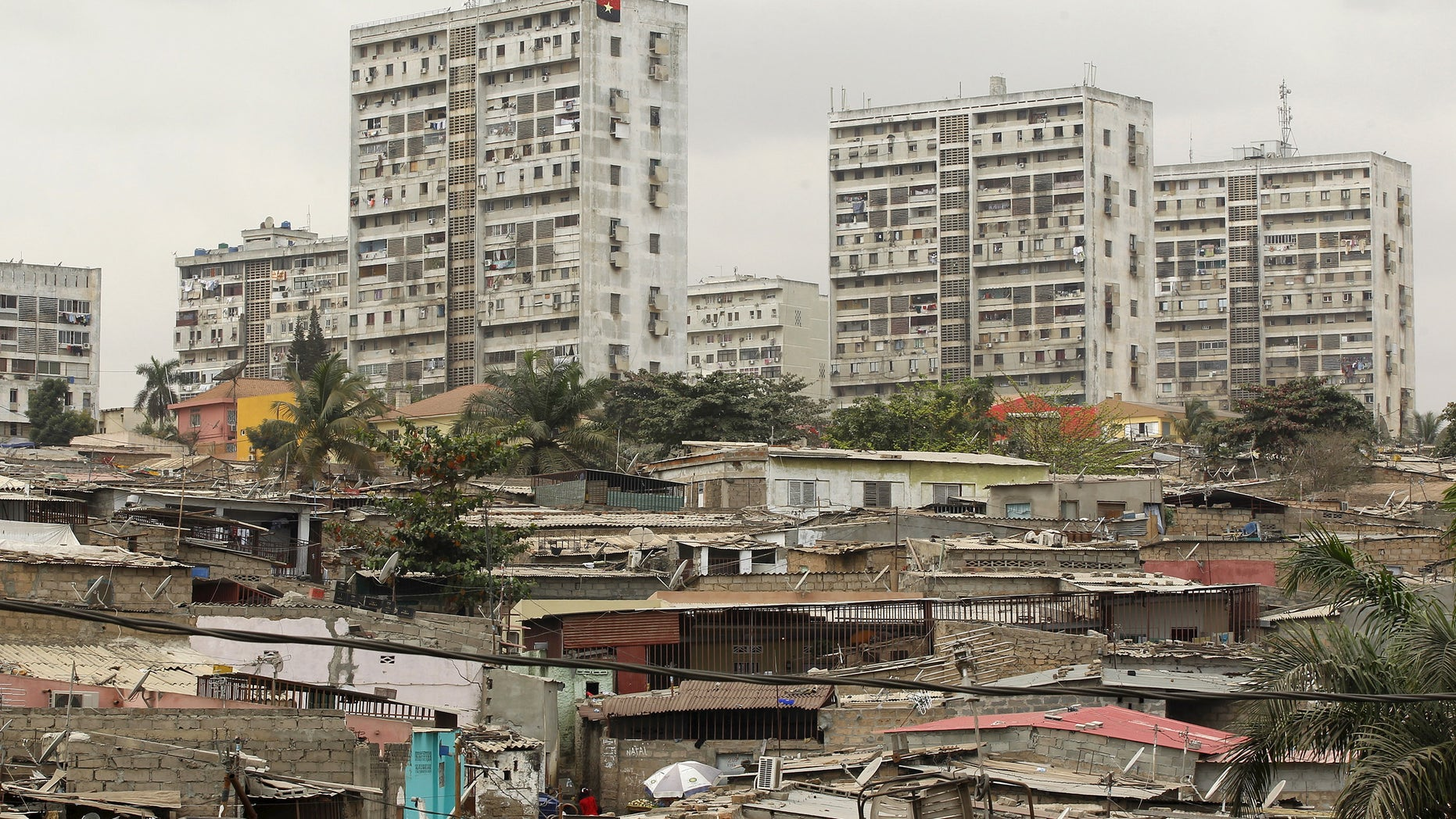 High-rise buildings are seen behind informal settlements in the capital of Luanda, in this August 30, 2012 file photo. REUTERS/Siphiwe Sibeko/Files - RTX2A2MP