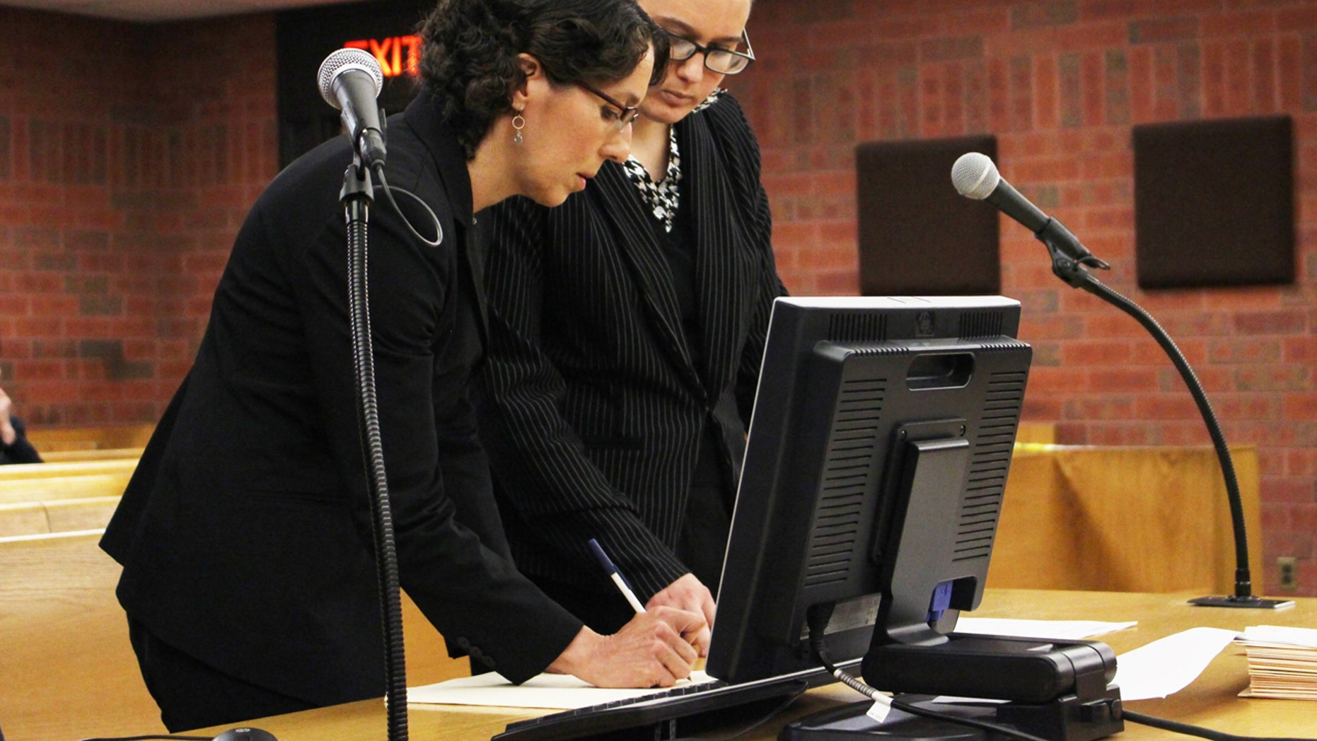 University of Connecticut law professor Jessica Rubin, left, and law student Taylor Hansen prepare to present arguments as animal advocates in a dog fighting case on May 30, 2017, in Superior Court in Hartford, Conn.