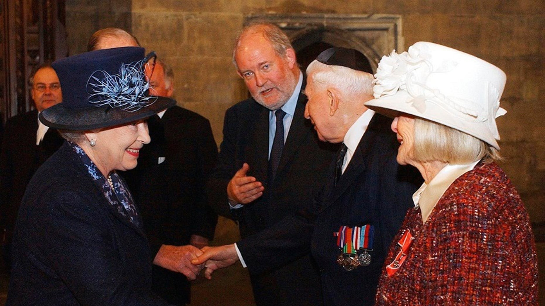 FILE - In this Thursday, Jan. 27, 2005 file photo, Britain's Queen Elizabeth II, left, meets Holocaust survivor Gena Turgel during a service to remember victims of the Holocaust in Westminster Central Hall in London on the 60th anniversary of the liberation of Auschwitz. Turgel, a Holocaust survivor who comforted diarist Anne Frank at the Bergen-Belsen concentration camp months before its liberation, has died. She was 95. Britain's chief rabbi, Ephraim Mirvis, said Turgel died Thursday, June 7, 2018. (Kirsty Wigglesworth, Pool Photo via AP, File)