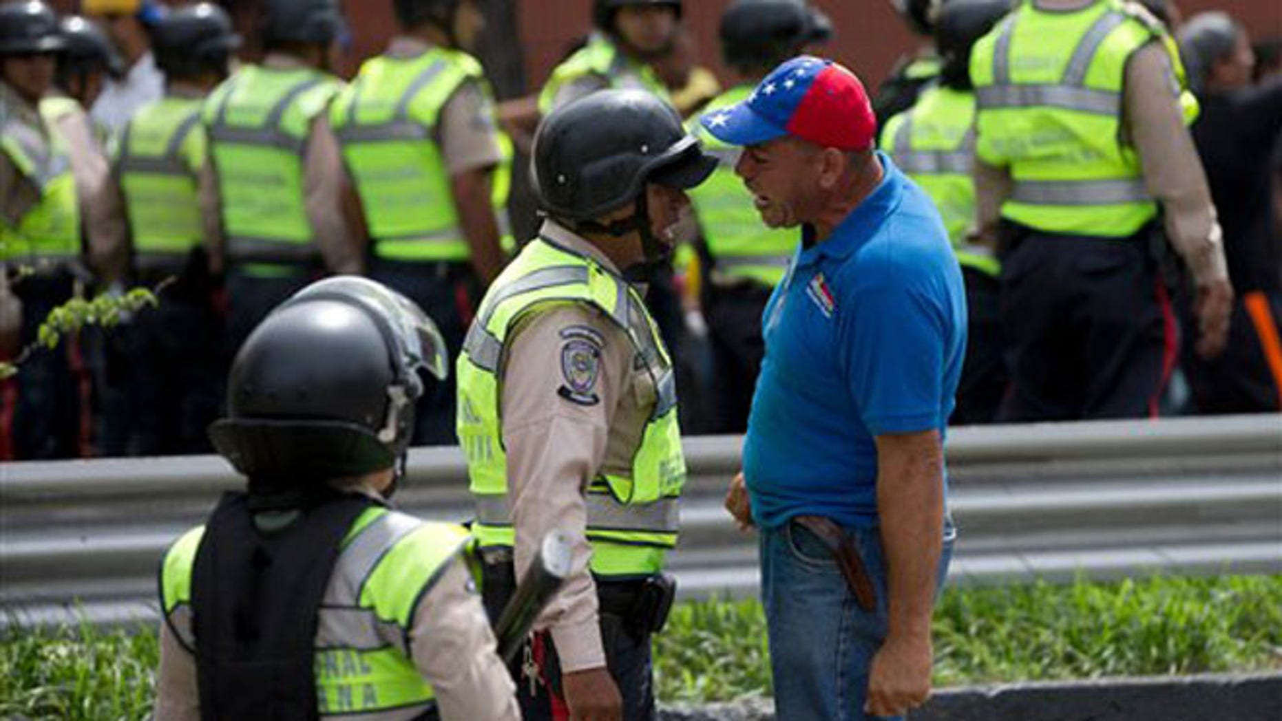 An anti-government demonstrator argues with a Bolivarian National Police officer during a march toward the headquarters of the national electoral body, CNE, in Caracas, Venezuela, Wednesday, May 18, 2016. The opposition was blocked from marching to the CNE as they demand the government allow it to pursue a recall referendum against Venezuela's President Nicolas Maduro. (AP Photo/Fernando Llano)