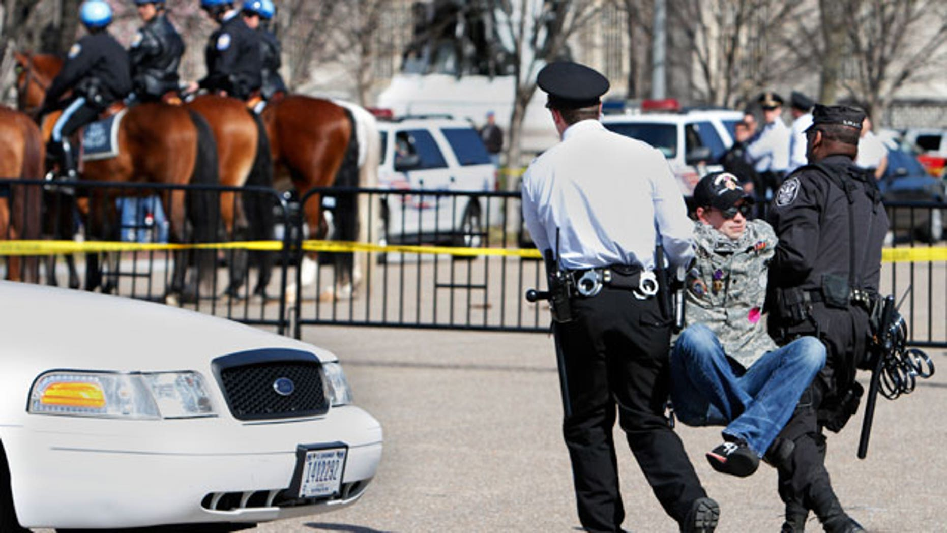 A unidentified protester lifts his legs as he is arrested by U.S. Park Police near the White House while protesting against war on the 8th anniversary of the Iraq invasion in Washington, on Saturday, March 19, 2011. (AP)