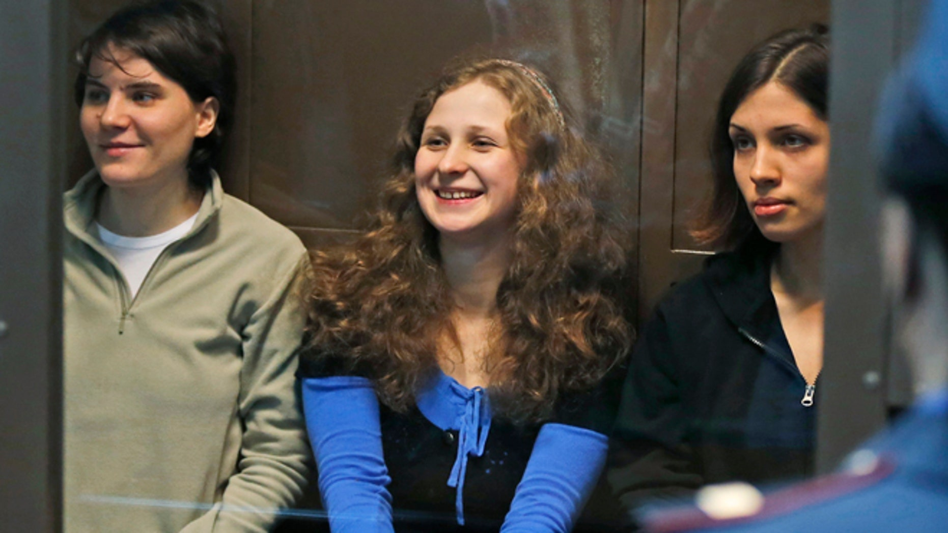 Oct. 10, 2012: In this file photo, feminist punk group Pussy Riot members, from left, Yekaterina Samutsevich, Maria Alekhina and Nadezhda Tolokonnikova sit in a glass cage at a court room in Moscow, Russia.