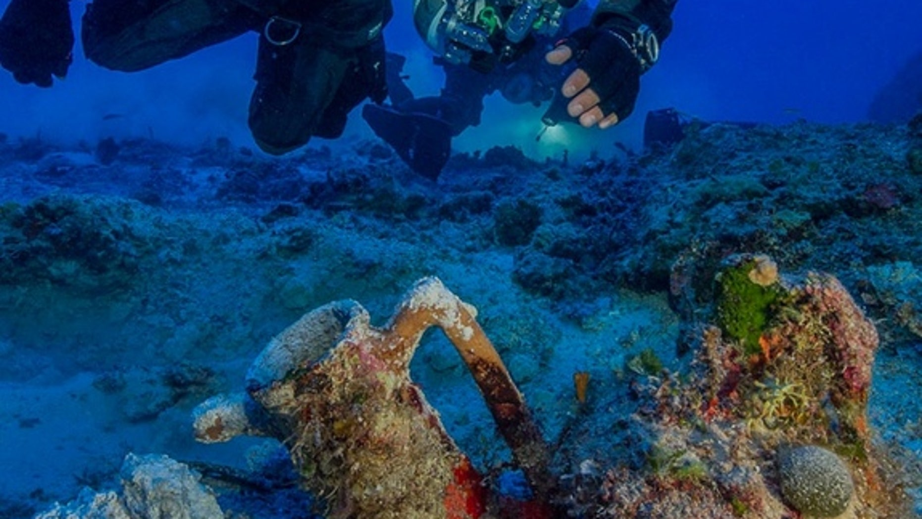 An archaeologist swims over artifacts at the site of the Antikythera shipwreck. In 2015, researchers pulled 50 new objects from the depths as part of the first scientific excavation of the wreck site.